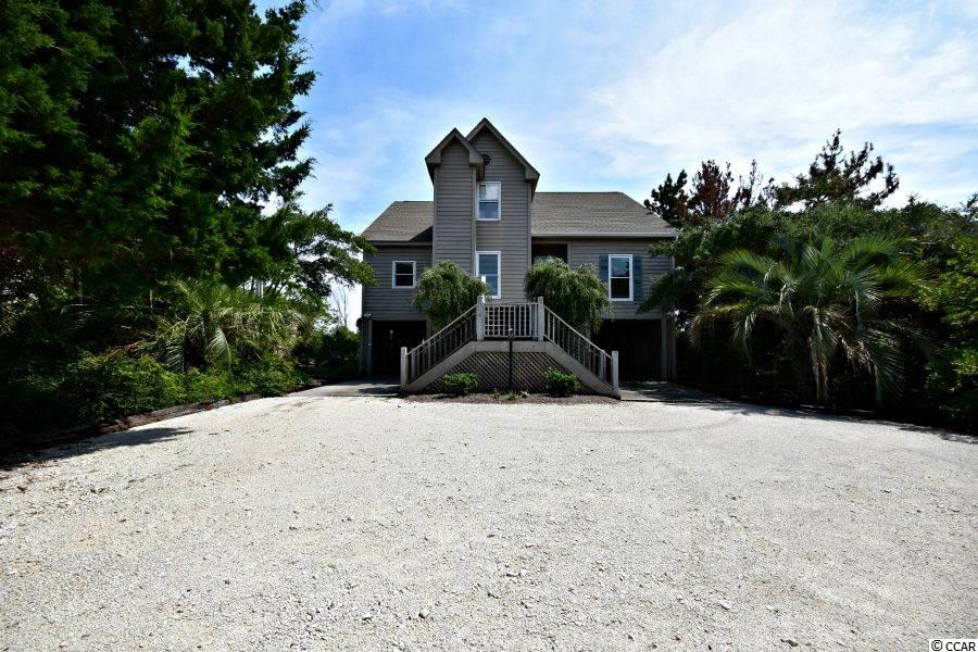 OCEANFRONT on a deep lot in great neighborhood.  Over 1500 sq. ft. of porch & deck space overlooking the ocean & North Litchfield Beach.  Hardwood, carpet & tile flooring, fireplace, walk-in wet bar, large kitchen/dining area with breakfast bar, sitting area in loft space on second floor, 3 first floor bedrooms, elevator, and ample parking & storage.