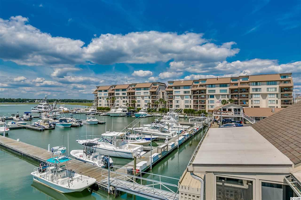 BRING ALL OFFERS!!!   GARAGE INCLUDED AND A STORAGE ROOM!!!  ACROSS THE STREET FROM THE BEACH.  Top floor.  A delightful and spacious unit overlooking the beautiful Marlin Quay Marina, gorgeous boats, sunsets, Murrells Inlet and even the ocean.  Enjoy Gulf Stream Cafe just steps away for dinner, swim in your two pools and walk across the street to the ocean.  None better.  OK, so this place is just AMAZING.  Did you see the pictures???  Did you also see a GARAGE is included?   All Many Marlin Quay units do not have garages, so this is a coveted item.  Has a separate storage room too.  Dern, rarely does a top floor, penthouse kind of unit come available and now there are two available, but only this one has a GARAGE!.
