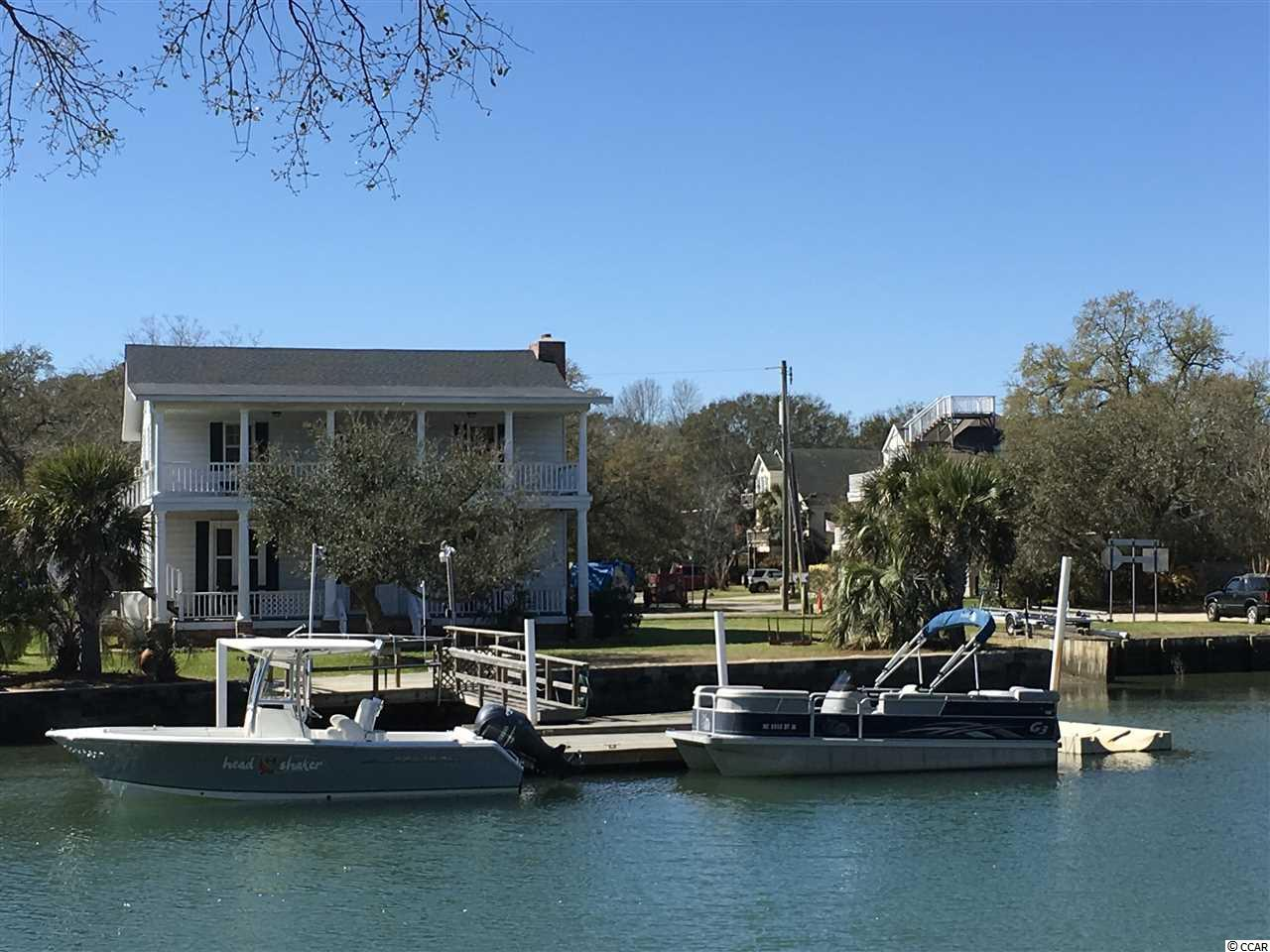 You Will Immediately Fall In Love With This Creek Front Home. Unique Beach Home with 103' of Direct Channel Access. This Home Radiates History and Fond Family Memories. Privately Owned BOAT RAMP. Not to mention a Stationary Dock - 16 x 14, 2 Floating Docks - 48' x 8' and the 2nd Dock - 16' x 10'   with a Walkway 16' x 3'- AND a Concrete Sea Wall.  Plenty of Room to Dock Several Boats. The Yard is a Great Size for Children Playing or Family Games and Barbecues. The Stationary Dock is set up with a Utility Sink to Clean Those Freshly Caught Fish as well as a Built in Bench.  All measurements are deemed reliable however, not guaranteed. Buyer(s) responsible for verification.  Interior Completed with Reclaimed Wood from a Church and a Railroad Station in Marion. 7 Bedrooms Total and 4 Baths, 2 Laundry Rooms and 2 Family/ Bonus Areas.  Great Place to Gather the Entire Family for Memorable Summer Parties and All Year Round Gatherings.  DIRECTLY on the INLET and Five Minutes Away From  Restaurants,Entertainment and The Inlet Marsh Walk. Amazing Views of the Inlet from Both 34' Porches and a Wonderful Balmy Breeze Off the Inlet.