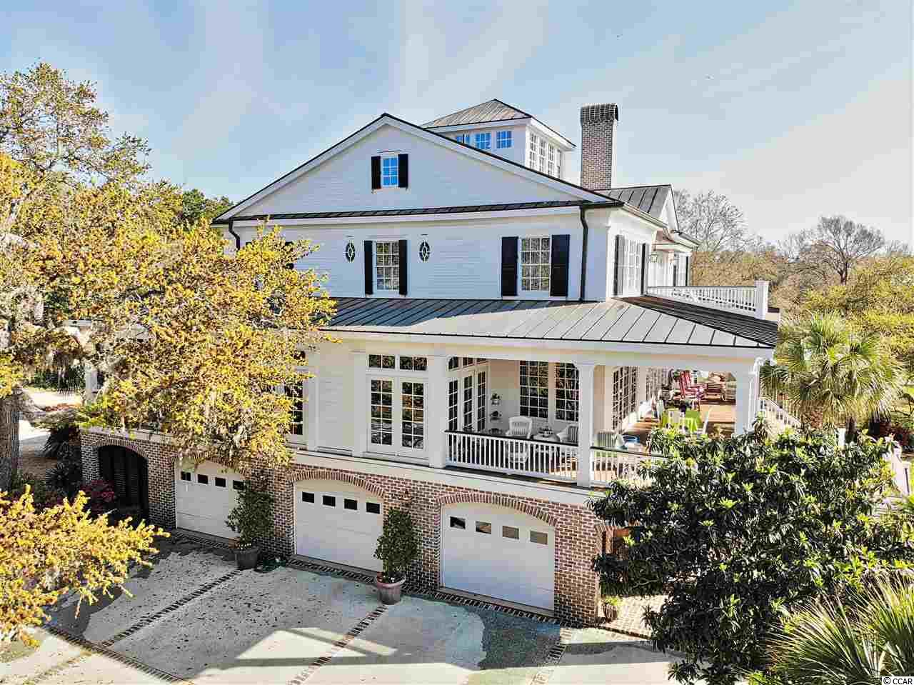A Jewel of the Lowcountry! This Absolutely Stunning Property is located on a Double Waterfront Lot Overlooking the Marsh and Ocean in Murrells Inlet. Spacious 5 bedroom, 4.5 bath, 2 kitchen, 3 story home plus a cupola that offers views all the way to the ocean and up the coastline. One of the few properties in the area with Deep Water Access even at low tide, this Plantation style home custom built in 2003 boasts extensive upgrades and is on an historical property. Surrounded by gorgeous landscaping and historic Live Oaks, it has an Oversized Heated and Cooled 4 Car Garage with Expansive Work and Storage area, Private Boat Ramp, Dock, Floating Dock, and Boat Lift. Features 12 foot wide Wraparound Porches, reclaimed 250 year old heart pine flooring throughout, granite countertops, 2 Upgraded Chef's Kitchens & elevator. 10 foot ceilings, custom hand carved woodwork, mantles, cabinetry and furniture throughout. Beam and coffered ceilings, gas and woodburning fireplaces. Downstairs den and porticos made from hand hewn cypress and Charleston brick, featuring cypress walls, custom cypress cabinetry and stainless steel appliances with commercial grade range. Structural upgrades include galvanized copper roof, reinforced solid poured concrete and steel block walls on the ground floor, laminated beam structure flooring system, retractable stainless steel hurricane shutters and all stainless steel nails throughout house. Features a fantastic layout with tons of Natural Light and Extensive Storage Area.