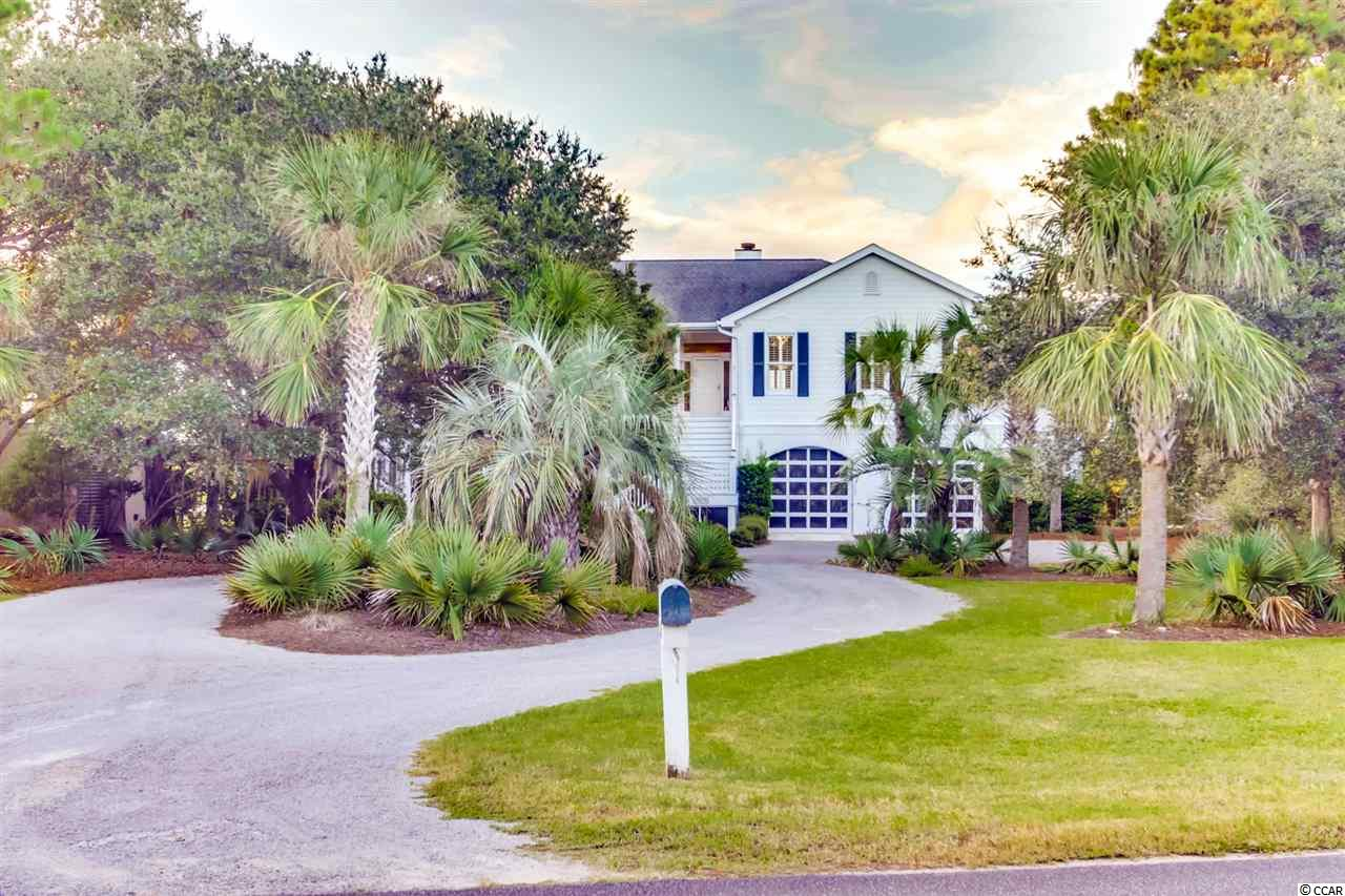 Wonderful raised ranch home in DeBordieu Colony with lots of space and an incredible view from the rear porch of the lake and clubhouse.  This WONDERFULLY decorated four bedroom home has a large great room and dining room.  All one level with lots of space to relax. Large dining table, washer/dryer, separate ice maker, plantation shutters and hardwood floors throughout.  Amenities include pool table, ping pong table and all furnishings convey.  Two full masters with ensuite bathrooms.  This house features a full garage underneath the house with space for boat and golf cart parking. This super house is great for entertaining and is located just off the main drive into DeBordieu Colony.  A short golf cart ride to the beach and pool.  Freshly painted exterior and well maintained landscaping make this house really stand out.