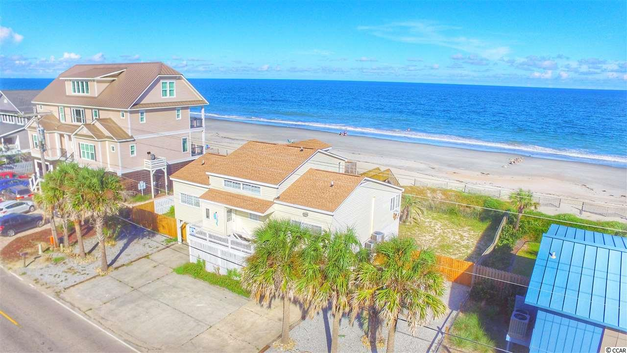 """One of the widest lots in Garden City Beach boasts this classic oceanfront cottage. 3 levels to give the family room to roam and large outdoor area is """"calling for a pool"""". High dune line and groin out front makes this south end location ideal.  Home is comfortably furnished and ideal layout for beach relaxing.  3 oceanfront bedrooms and 3rd floor master features private walkout deck to enjoy morning coffee.  Expansive Oceanfront Carolina Room is ideal for dining, card games, or simply taking in the breathtaking ocean views. New walkway leading to beach even features a shower to rinse off before coming in! Short walk to the Point and Jetties to watch boats heading out for some deep seafishing."""