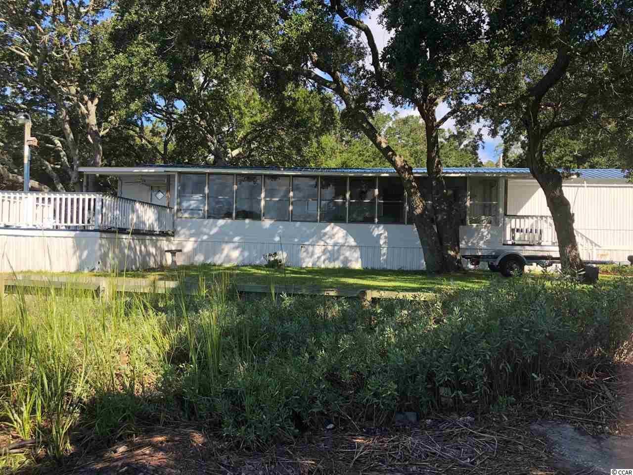 Marsh Front with breathe taking view of sunsets and wild life. Spacious mobile home with a sunroom and deck for panoramic view of the water. Boat ramp access, public pier for park owners, boat trailer parking lot, and public gazebo are free amenities. Home has a storage building for Golf Car storage. All appliances convey and home is partly furnished which makes it move in ready. Newer Metal roof, HVAC, and Insulated windows. Yearly lot lease includes land taxes, trash pick up, yard maintenance, water and septic sewer. Come see!