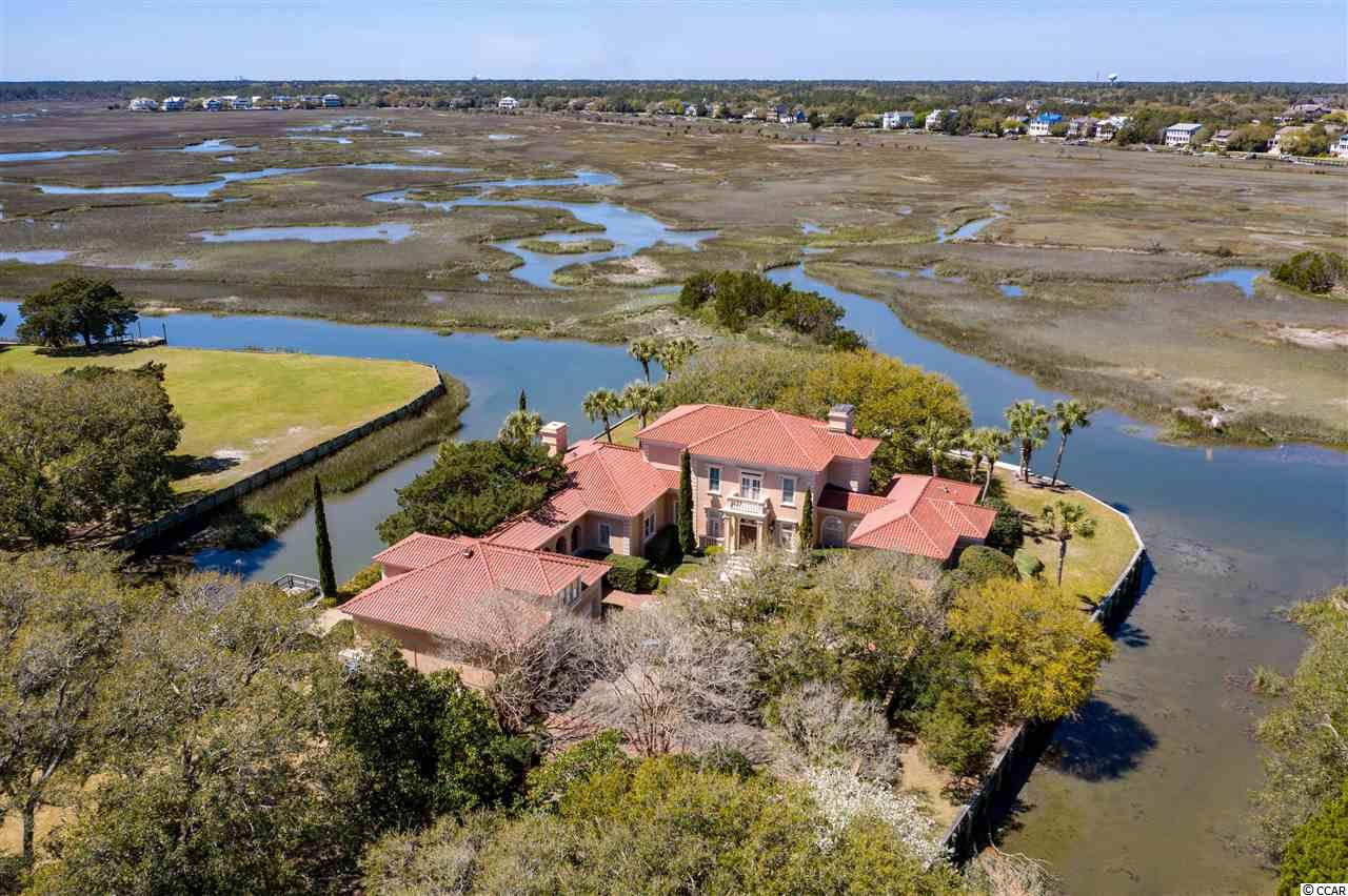 This Mediterranean style home is in perfect harmony with its inspiring surroundings. The tranquil Lowcountry setting is quite unique. Enter the compound through a gate, and you are on your own private peninsula surrounded by saltwater. The auto port and three car garage provide plenty of space and storage for an active lifestyle. Inside and out the home is classic with a European inspiration. Custom craftsmanship is noted throughout this timeless home. It is spacious offering both a formal and casual living space. The private master bedroom suite with two separate bathrooms and the closets is on the 2nd floor serviced by the custom circular staircase or elevator. Suiting many lifestyles, this residence is impressive, yet simple. The main house has three bedrooms. A separate and spacious guest house with its own kitchen is located above the garage. There are a total of four bedrooms, five full baths and two half baths. The property is truly private sitting off of DeBordieu Boulevard on a discreet road leading to the gated entrance. The island like setting is bulkheaded and has two docks for Lowcountry living. Located on the creek yet close to the beach is another reason to see this property and to understand just how special it is.