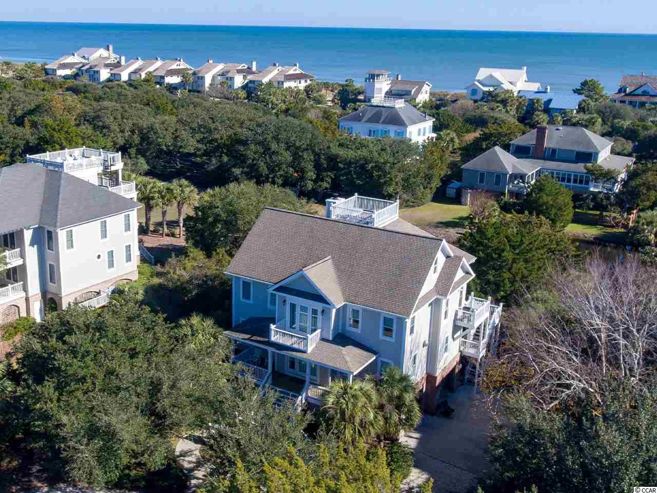 Open the doors and hear the ocean waves rolling in. Inviting you to come walk and play on the beach just a few steps or bike or golf cart ride away. Or lull you to sleep at night or a relaxing afternoon nap. This beautiful 3rd row home has ocean views and sits on a lake to the east and a lake to the west. Open floor plan with plenty of bright refreshing space and 7 bedrooms and 6 baths. 4 Bedrooms down with a playroom/den. Master and open great room/dining/kitchen up. Huge screen porches up and down on the ocean side and an open porch at the front door to the west. 2 bedrooms next floor up share a bath. Keep heading up another flight of stairs to the rooftop deck offering 360 degree views of all of DeBordieu and the ocean and creeks. Just a short exciting golf cart ride to the oceanfront Beach Club which offers fine and casual dining, the Blue Heron Beach Grill, Gazebo Tiki Bar, two pools and a playground with basketball and volleyball court. DeBordieu also offers The Golf Club with the private Pete Dye golf course and Tennis Center and Fitness Center. DeBordieu encompasses approximately 2700 acres of natural beauty from the ocean and beaches and wildlife and woods to the creeks and North Inlet. Excellent boating and fishing ! Biking and golf carts ! Beautiful sunrises and sunsets ! Family fun and activities are endless ! DeBordieu is all safe and secure with a 24 hour manned security gate. Located just 30 miles south of Myrtle Beach and 60 miles north of Charleston ! Come live the life that makes DeBordieu, DeBordieu !            A place where man and nature live together in harmony !