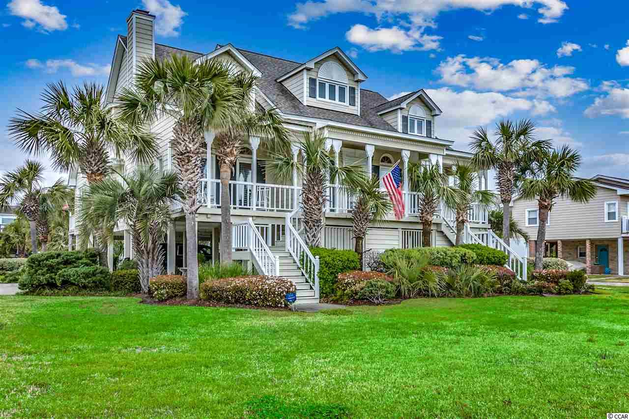 This 3br/3.5 bath raised beach home located in the absolute heart of the prestigious Ocean Drive & Tilghman Estates area section of North Myrtle Beach is in excellent condition and ready for it's new owner.    When you sit down to relax on your front porch, you will be taking in some of N. Myrtle Beach's best ocean views.    This custom built home has only had one owner and has been extremely well cared for.   From the moment you pull up to this great home, you are greeted with a spacious  corner lot with room to spread out and professional landscaping.   When you walk through the front door, you are greeted with gorgeous heart pine wood floors running throughout the entire home(except carpet in the bedrooms).   Cathedral ceilings, lots of windows with plantation shutters allowing in tons of natural light, wet bar, and a gas fireplace offer you a beautiful living/family room for your entire family to spread out.   As you walk into your spacious kitchen you are greeted with tons of cabinet and counter space, lots of windows for tons of natural light coming into the house, and a breakfast nook right off of the kitchen.    If you are someone who likes to entertain, make sure to use the formal dining room for all occasions.    The master bedroom is located on the first floor of this home offering large his and her walk-in closets.   As you enter the master bath, the skylight allows so much natural light in.  It also boasts dual sinks, vanity, walk-in shower, and a whirlpool tub.  Your family or guests will enjoy their own bedrooms and private baths upstairs.   If you are someone who likes to work from home, make sure you set your office up in the loft upstairs in front of the window that gives you endless ocean views.     You have to see it to understand!     Some of the other great features of this home are:   New Roof 2018, HVAC approximate 3 years old, extra large storage under this home, great use of all space for storage throughout this home, tons of room for addit