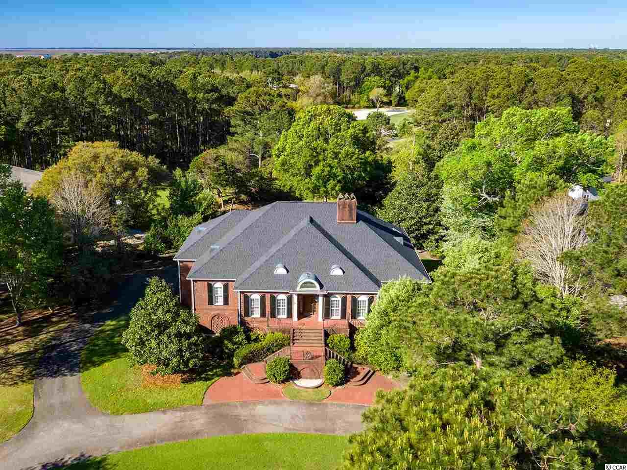 Stately and elegant, close to the beach, on over an ACRE, 2610 Wallace Pate is the perfect DeBordieu Colony home for the family who likes to entertain! This beautiful, low-maintenance, all brick, estate on the golf course is the perfect primary residence or vacation home! Your elevator will take you, your luggage and your groceries from the garage right up to the main hall, convenient to the kitchen and master suite! The entrance from the circular driveway is truly grand, with a split staircase trimmed with wrought iron railings leading to the welcoming front door. The wide, foyer features a lighted barrel ceiling, beautiful wainscoting, and dental molding, with formal living and dining rooms on either side. The center island kitchen with an abundance of cabinets and a wet bar is partially open to the huge den with gorgeous cypress paneling, coffered ceilings and fireplace. Enjoy the abundant outdoor living spaces on the 2 covered porches, deck, and large screened porch right off the kitchen. The spacious master suite features Her bathroom with a whirlpool tub, His bathroom with a walk-in shower, two walk-in closets and a linen closet. Also on the main floor are two guest suites, each with their own private baths, a large laundry room with storage, and a powder room. Upstairs you'll find the 4th bedroom, full bath, extra bunk room and plenty of storage.  The floors are hardwood in the living areas, carpet in the bedrooms, and tile in the main floor baths. The garage area features plenty of room to park cars, boats, golf carts and bikes, and a convenient, enclosed outdoor shower to wash off the sand from DeBordieu Beach, just a short golf cart ride away. DeBordieu Colony is an oceanfront community located about an hour north of Charleston, South Carolina, just south of Pawleys Island, featuring access to over 6 miles of secluded beach, private Pete Dye Golf, a Tennis & Fitness Center, an Ocean Front Beach Club with casual and fine dining, saltwater creek access to No