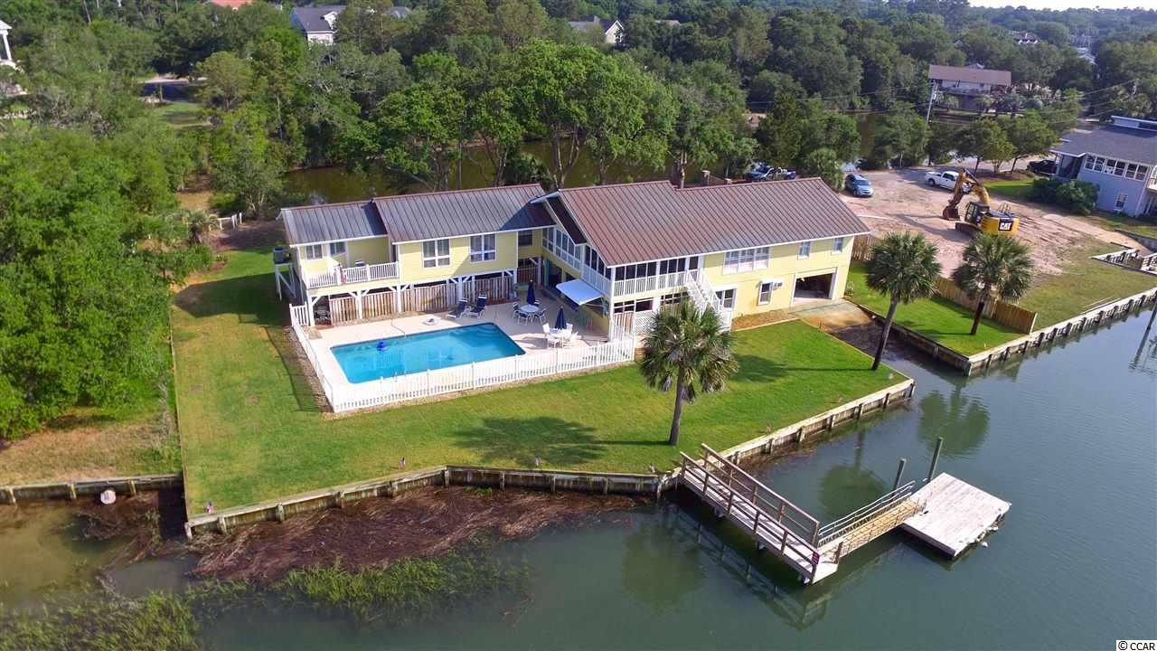 """This beautiful stately home is located on deep water in the heart of Murrells Inlet. Once you enter the private gates, you will be amazed by the privacy and  shear size of the lot. With 160 feet of creek frontage, this 4 bedroom 3 bath home gives you all the options that you need to be able to spread out! The North wing features two guest rooms and a full bath, all with amazing views of Murrells Inlet. The central part of the home has the kitchen, dining area, living room, and a serene screened porch; and guess what... they all have amazing creek views! The newest addition is the Southern Wing which features the Master suite, a private office, a private balcony, and a Master bath room that has views that will rival any bathroom in the world! The home features hand crafted real wood floors in the main living areas. The beautiful copper roof protects the home while also providing an beautiful look. Downstairs you will find the final bedroom, which is currently being used as the workout room, as well as a full bath and the laundry room. The ground floor level does has flood insurance coverage as this home was built Pre-Firm and it is grandfathered in to the program. In the backyard, you will quickly learn that this home was built for entertaining. Whether you are hanging out on the couches, the bar, or summer kitchen area in """"Margaritaville""""; dipping your toes in the large pool; or hopping on your boat for a sunset cruise; you and your friends will enjoy the tropical vibe of this creekfront home! The home also features a state of the art security system. Did I mention there is 160 feet of creek frontage and a private boat ramp? This home has it all. Call today for to set up a private tour."""