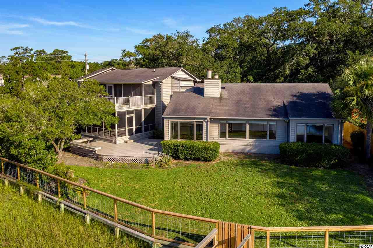 """Check out the million dollar view! This timeless home offers a view that's absolutely breathtaking. The Inlet lifestyle is what most dream about. From the relaxing screened porch, new floating dock and boat lift, separate mother-in-law suite, and true southern landscape boasting live oaks, you may never see a home like this again. Hop in your boat or even paddle board to the nearest freshest seafood around at the Murrells Inlet Boardwalk. Nestled away in a quite small community, you will feel you have found your own slice of paradise. With the long tree lined private driveway leading to your new home, you may never want to leave. The moment you walk inside, you will fall in love with the gorgeous inlet views.  This home was built for entertaining with an open main living floor plan, even including a butlers kitchen. There is a family room/game room with a wet bar leading out to the screened back porch. Upstairs you will find 2 more bedrooms, a his and hers bathroom and a perfect room for a """"Hollywood closet"""". There is a space upstairs that would be perfect for a home office as it has its on separate entrance and wet bar as well. There is a central vacuum system set up for easy use throughout the home."""