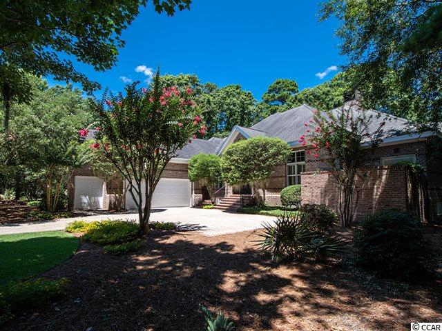 Price Improvement! Classic beauty blended with southern gentility describes this custom brick home in DeBordieu Colony. Designed by Wayne Rogers of Catalyst Architects, this comfortable home features custom cabinetry by Bill Blakely of Classic Touch. Step through the mahogany door into a marble-floored foyer and your eyes are immediately drawn to the golf course view through oversized windows at the end of the large living room.  With 12-foot ceilings, the large living room has hardwood floors, a Blakely designed mantel over the gas fireplace and French doors that lead to the spacious screened in porch. The wide screened porch with slate flooring overlooks the 15th green on the Pete and P.B. Dye championship golf course. A marble-floored formal dining room just off of the living room has extra-large custom designed corner cabinets and chair railings. The open concept kitchen features a large central island, Sub-Zero refrigerator, 4 sinks, filtered drinking water system, skylight, desk, wet bar with Sub-zero bar refrigerator/freezer/ice maker. Plenty of upper and lower cabinets as well as a pantry and a cabinet to store recycled materials make storage easy. The kitchen is open to the family room with its built in bookcase and entertainment center. This space includes a casual dining area with spectacular views of ponds and wildlife surrounding the lush golf course. The master bedroom has its own private space on one end of the home and includes a gas fireplace, French doors to the screened porch, walk-in closet, cedar cabinet above the linen closet and a skylight. The master bath features a double sink vanity area, stained glass window over jacuzzi tub, walk-in shower, heated tile floors, separate water closet, ceiling fan and lighted skylight. There is a smaller bedroom/office space area around the corner and two more bedrooms on the opposite side of the house with bathrooms to accompany them. Upstairs is a large bonus room/5th bedroom with 2 built in work-spaces, w