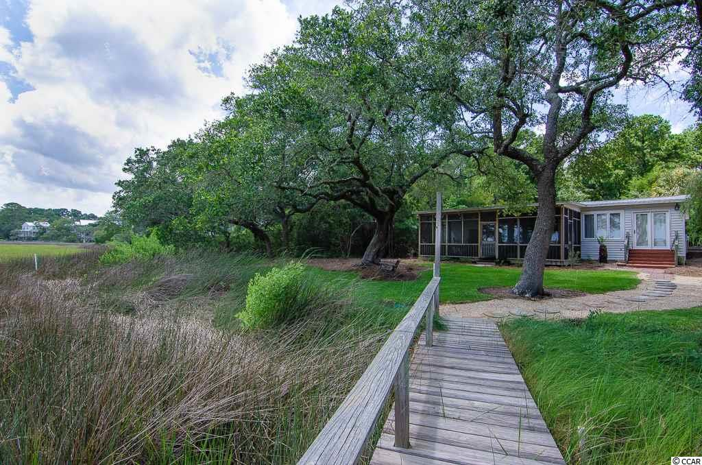 "Waterfront creek-house in Pawleys Island with a dock! And it comes furnished! Welcome to 30 Furman Ln., located directly on the beautiful saltwater marshes of Litchfield Beach and Pawleys Island. Load up the family for a day of flounder fishing in Pawleys Creek or ride the boat over to the ""Creek Beach,"" a hidden stretch of beach where the locals play in the warm months. 30 Furman Ln. has 3 bedrooms, 2 full bathrooms and wood flooring throughout. The kitchen is spacious with plenty of cabinetry and barstool seating. Featuring an ""open-concept"" layout, the home's kitchen transitions nicely into the living room, which has smooth ceilings and crown molding and flows directly into a sun room overlooking the salt marsh. The master bedroom has views of the water and a sliding door that leads out to a large, screened-in deck along the marsh. You'll notice the guest bedrooms are tastefully decorated, one of which includes 4 bunk beds for accommodating children or additional guests. Oyster roasts and cookouts will be a dream in this back yard, with sweeping views of the saltmarsh and a swinging bench tucked under the live-oaks. The property also has a storage barn and ample parking. This is your chance to own a creekfront property with a dock in Pawleys Island at an unbelievable price-point."