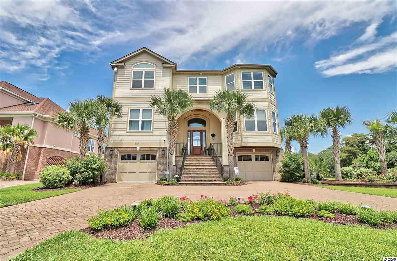 "Welcome to this Stunning 4 Bedroom, 4.5 bath Custom Built Raised beach home. This Beautiful home is on a large lot, adjacent to Dogwood Lake on the North End of Surfside Beach! Custom Marble tile entry & 18"" Inch Marble tile Kitchen Floor. Thermador Appliances include double oven, microwave, & cooktop range. The Thermador Dishwasher, Refrigerator & Separate Freezer have cabinet door fronts making the Kitchen look simply elegant! Grocery Pantry & Butlers Pantry, the soft close Drawers, Top Lighted Glass Front Cabinets Stacked on 42"" cabinets with lighting underneath are complemented by the Granite countertops & Detailed tile backsplash. The Touch Faucet, Instant Hot Water at the sink, Breakfast Bar, Large Breakfast area & Formal dining room are ideal for entertaining. A 3 Dimensional Fireplace sits in the center of the Kitchen, Breakfast area &  Great room. The Great/Family Room is a real stunner with the Hardwood floors, high ceilings, windows all the way up, French doors, (Fixed & Functional) & Built in Custom Entertainment Center. The hardwood floors continue up the stairs, on the landing, & down the foyer. Each bedroom features its own private bath, Hardwood floors,Large closets, ceiling fans & upgrades through out. The Master Suite has it all, Vaulted Ceiling, Ceiling Fan, Surround sound, Double Walk in Closets with Built ins, a Sitting Room/Office with Vaulted Ceiling, additional closet space. Step into the Master Bath & you will see the Large Tile Shower with a Rain Head, 2 shower heads, 4 body jets & built in bench, Double Sinks, Vanity, Linen closet & tile floor. All this & a Private Covered Porch, Spiral Staircase to the Widows Walk overlooking Dogwood Lake & an Ocean view! Definitely an fabulous Master Suite! Bedroom 2 Beautiful Hardwood floors, walk in closet with built ins, Large Custom Tile shower Large vanity & sink! Bedroom 3 Is currently being used as a media room & the private bath features a Bubble Tub with a tiled walls, & ledge. Bedroom 4 also features a private bath with a custom tile shower. The right garage bay goes to the back of the home & the left goes about halfway back . There is an enclosed bonus area that leads out to the spacious covered porch, Built in grill, countertop/Bar area that overlooks the beautiful saltwater pool & spa. Tastefully landscaped, paver Driveway, paver pool decking, all decks are Trex, interior & exterior sound systems, state of the art security system, gorgeous long lake views, steps to the Beach & so much more!!! No HOA!! This home will not last long, call for an appointment today!"