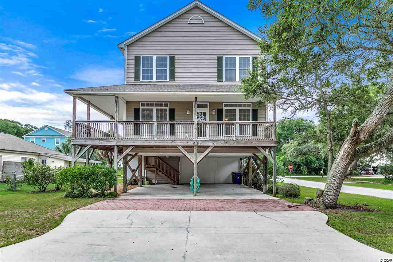 Closing scheduled for 9/3/19. 21 South Oak Drive is a semi-detached four bedroom, three bathroom, two-story raised beach house with approximately 1680 heated square feet and about 800 feet to the beach. The exterior is low maintenance vinyl siding, has covered parking and an attached ground level storage room. The open interior includes a large living and dining area, kitchen, laundry room, bedroom, and full bathroom on the main level. The wrap-around covered porch has access from the living room and bedroom. Upstairs there are three more bedrooms and two bathrooms. The floors are laminate wood, carpet upstairs, and tile in the bathrooms and kitchen. The heating and air conditioning were replaced in 2016. The home is situated steps to everything in Surfside Beach, including the pier, restaurants, Fuller Park, the dog park, tennis courts, and the library. You can walk or golf cart everywhere you need to go. Why continue to rent when you can own a piece of one of the most beautiful stretches of the Grand Strand?