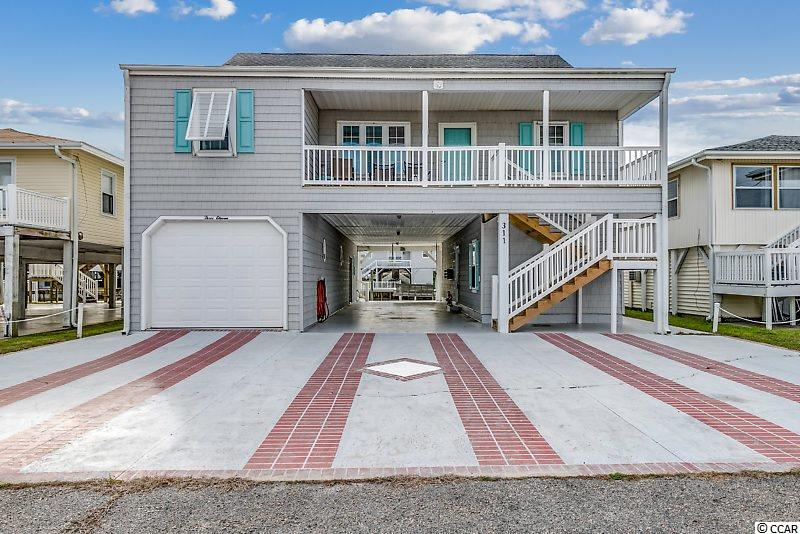 Wow! 4 bedroom, 4 bathroom, fully-furnished, large channel home built in 1996 in the Cherry Grove section of North Myrtle Beach, just over a block to the beach with many upgrades and lots of things others don't offer. Also, a complete separate in law suite with it's own entrance, a bedroom, kitchen, living room and bath. This well taken of care primary residence home is on a wide channel with a floating dock with an aluminum ramp. Great views of the channel and even views of the Tidewater golf course from across the marsh! The spectacular, freshly painted home offers a large master bedroom with a walk in closet, spacious master bathroom, double sinks, tiled shower, large kitchen with nice cabinetry, large pantry, kitchen island, newer appliances, large living room and dining room, breakfast nook, hardwood floors, crown molding, sunroom with lots of windows overlooking channel, full size washer and dryer, steps and railings recently replaced, large (deep) garage with new opener, workshop, lots of room for parking cars/golf carts and hanging out, front porch, rear porch, useful elevator/lift from ground floor to sunroom, large attic space with plenty of room to stand (8'+) or to add additional living space. This is a great home with lots of space at a great price!