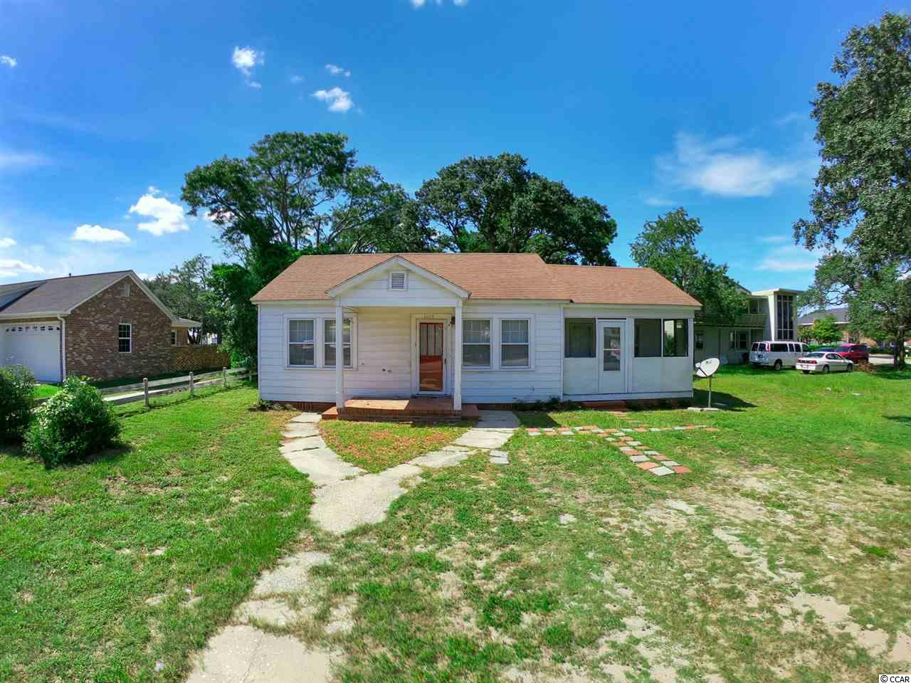 This amazing home is located just a short walk to the ocean and Myrtle Beach Skywheel. Right in the heart of Myrtle Beach, this 1/4 acre corner lot is close to all of the attractions including restaurants, amusement, and of course the beach! Inside you'll find fresh laminate flooring, and a split bedroom floor plan with a large master bedroom. Enjoy the ocean breeze from your screened porch off the master bedroom. A jack & jill setup for the guest bedrooms is perfect for visitors. This could make a great vacation home, investment property- and with the commercial zoning you could turn this large lot into a business opportunity. This is an excellent chance to own a piece of the beach!
