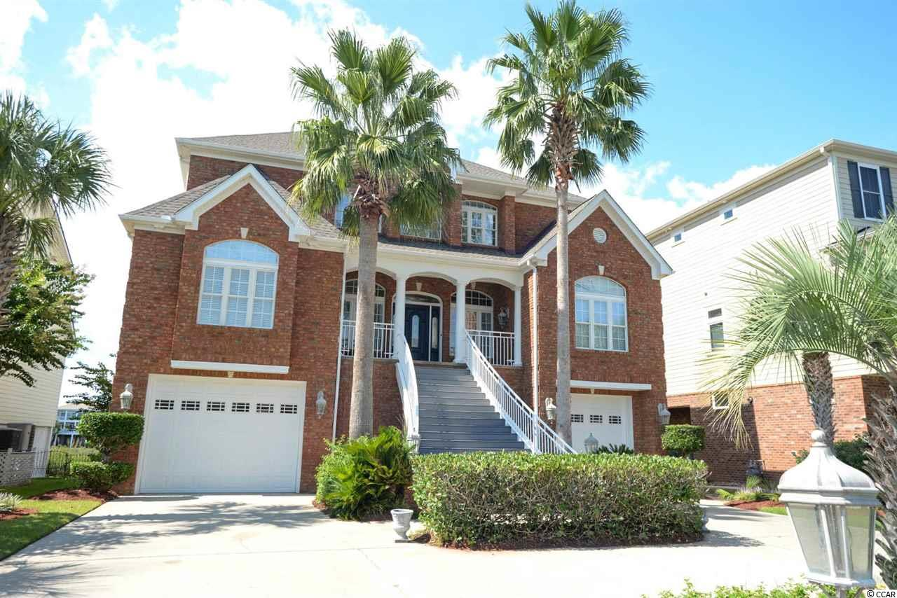 Wow! This 5 bedroom, 5 ½ bathroom, amazing home in North Myrtle Beach directly on the Intracoastal waterway in the Sunset Harbour neighborhood. Watch the boats go by from this spectacular three level home with an elevator with so many upgrades and features including spectacular views of the ICW from many rooms, wood flooring, high ceilings, beautiful crown molding, doors and door casings, chair rail, wide baseboards, coffered ceilings in the formal dining room, amazing cherry kitchen cabinets and built-ins, gorgeous backsplash, granite countertops, open kitchen, nice appliances, each of the large 5 bedrooms has its own bath, additional ½ bath for guests, top floor has the additional bedrooms and separate living room, game room and extra-large garage on first floor, central vacuum, large master suite overlooking the waterway with two walk-in closets, large master bathroom with double sinks, jetted tub, tile shower, bathroom cabinetry, granite in bathroom, gas log fireplace, wet bar, flat ceilings, oil rubbed bronze hardware, wood closet shelving organizers, large walk-in attic for storage, large laundry room, secondary bathrooms have tiled floors, nice toilets throughout, open plan with lots of natural light, large exterior steps leading to main level of home, interior steps, shared pier with private boat lift, lush landscaping in the front and back, circle driveway, brick light columns, brick accent wall, brand new roof, separate screened in porch, enormous deck on the back, patio, trex type deck in front and back, sundeck on top level with amazing views, brick and Hardie siding. Sunset Harbour is close to the beach, has a nice pool on the ICW, boat ramp and has gated boat/trailer storage. This home has it all!