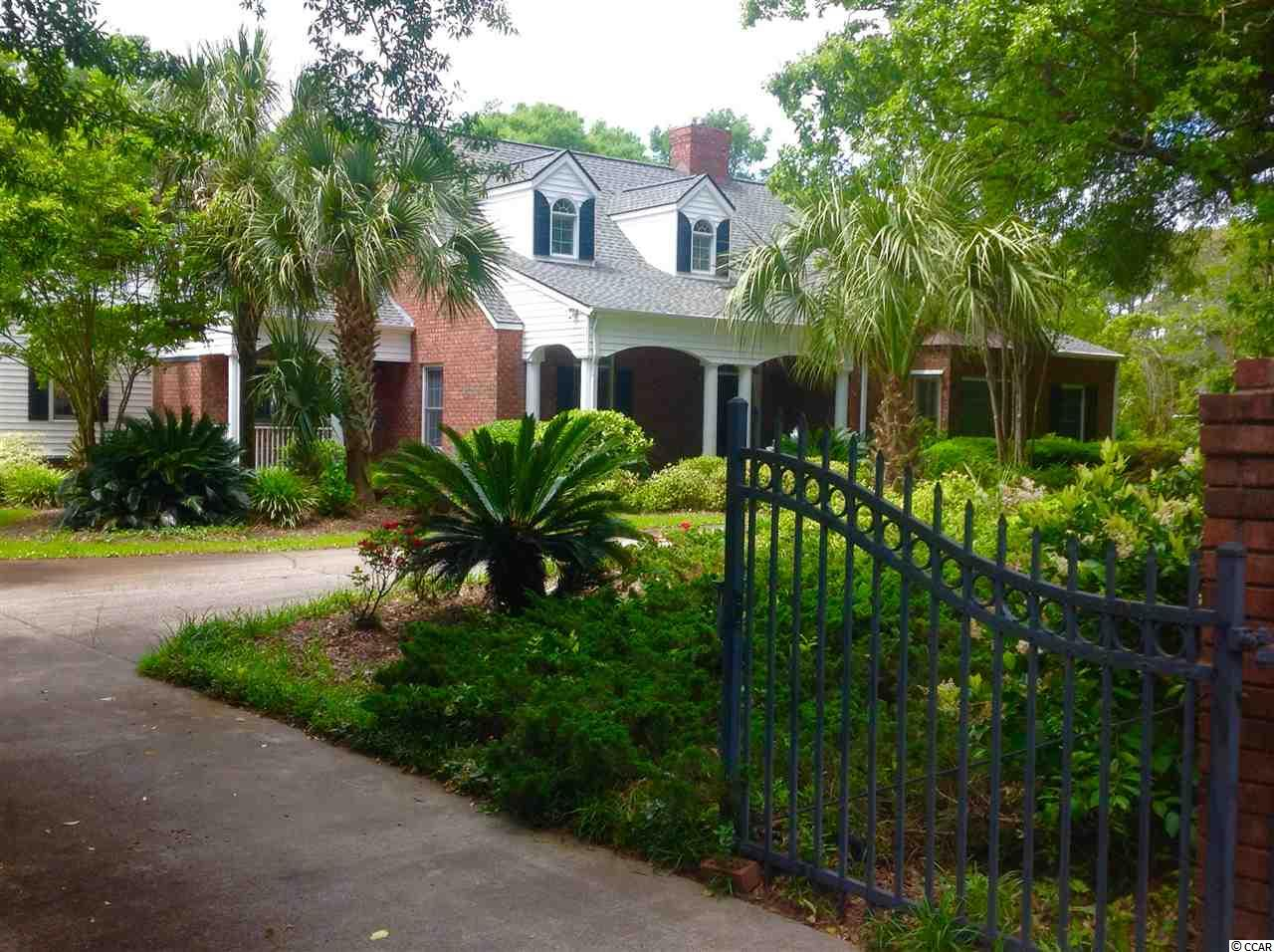 Beautiful, traditional brick home in the community of Arcadian Shores, just a stones throw to the Arcadian Shores Golf Course and a mere 3 blocks away from the Atlantic Ocean! Located in a very desired and very established neighborhood this home boasts a great room with vaulted ceiling,  built in shelves, a gas fireplace vented to the outside with a beautiful brick chimney surround added for decorative purposes. terra- cotta  tile on both front and rear porches. circular gated driveway lined with with mature majestic oak trees. Oversize porcelain  tile in foyer,kitchen and breakfast room.   Built as a good cents home to help keep the utility bills and the carbon footprint in check. The kitchen offers stainless steel appliances,  and a breakfast nook that leads to a screened porch. The large tiled patio outdoors offers the perfect space for people who love to entertain or just relax and soak in the South Carolina sun. There is also a bonus room upstairs with a full bath, closet, and some additional storage. Timberline ultra high definition roof was just recently installed in 2017.  This home features beautiful hardwood trees, Many mature palm trees, colorful mature azaleas, beautiful natural grown crepe trees adorn the over sized lot.  underground pump, pump house and irrigation system. This property is being sold as is, buyer is responsible for verification.
