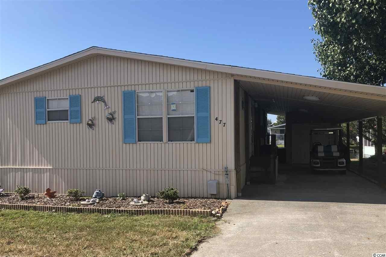 Beautiful well maintained furnished large lake front 2 bed 2 bath home water view home located in gated community of Oceanside Village. Large Carolina room full of windows and grand views overlooking canal and lush yard. Open concept Many updates including, new roof 2019, carport and attached storage building large enough to store golf cart,  bathrooms updated 2016, New flooring luxury vinyl tile in bath, kitchen, laundry, new lake wall 2019, new outside lighting 2017, oversize gutters 2017 Can be used as a vacation rental. Home includes access to Oceanside amenities including, private beach access and parking, 24 hour security, 2 outdoor pools, spa hot tub, splash pad, kiddie pools, heated indoor pool, library, fitness center,community center, basketball court, stocked fishing ponds, picnicking areas, volleyball court, bocce ball and horseshoe pit, and children's playground.