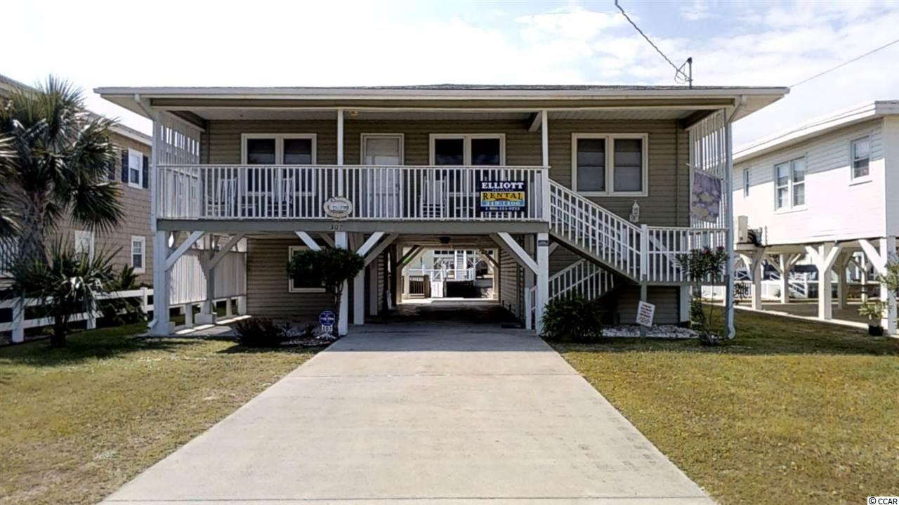 Absolutely charming raised beach home on the channel just a block from the beach in Cherry Grove!  After a day on the beach, rinse off in the outside shower and store your beach items in one of the large storage areas under the home.  Then enjoy dinner/cocktails along with beautiful views of the channel from your large rear porch or lower deck that sits right on the water.  Inside you will find open concept living.  The expansive great room offers plenty of room for entertaining.  Two bedrooms have a Jack and Jill bathroom and the third bedroom has its own on suite bathroom.  Other unique features of this home include original hardwood floors throughout, fully furnished with all appliances included, two large rooms under the home provide opportunity for storage or expansion, split bedroom layout and more.  Enjoy being in a quieter section of the beach while still only minutes from Main Street in North Myrtle Beach.  Convenient to dining, shopping and entertainment.  Don't miss this opportunity!  Be sure to check out the all immersive 3D virtual tour and schedule your showing today!