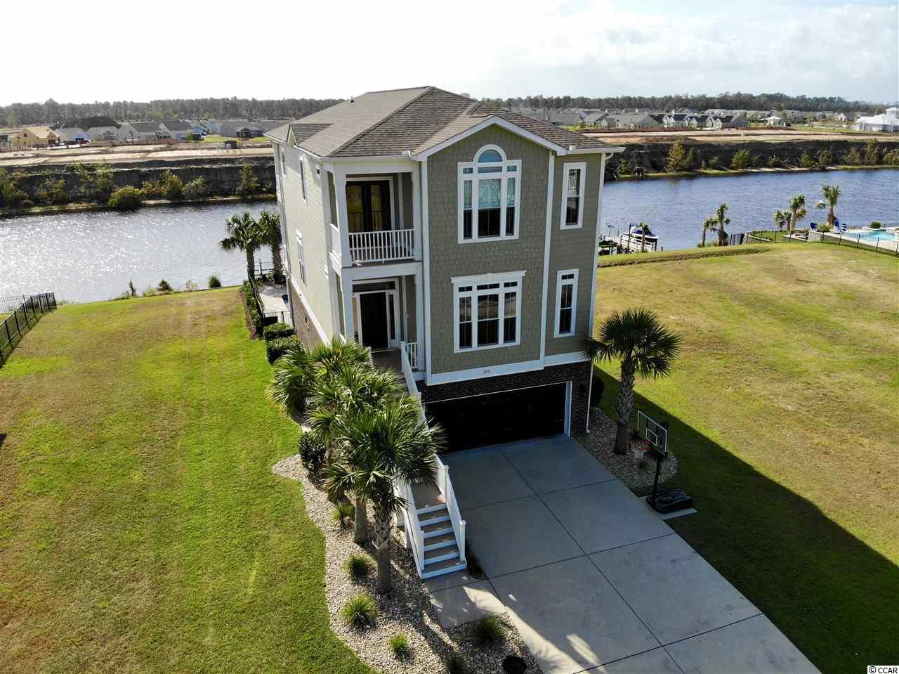 Exquisite 5 bedroom 4 bath home on the Intracoastal Waterway in the charming community of The Battery On The Waterway! This immaculate home is 3 stories with an elevator and has a rear porch on every story to enjoy those picturesque views of the waterway! Beautiful hardwood floors and crown moulding run throughout the main living areas. The main floor, which is the second floor, hosts the open concept living, dining, and kitchen. In the gorgeous kitchen there are stainless steel appliances including a gas range, a large walk-in pantry, granite countertops, and plenty of cabinet space! There is also an oversized work island with butch block countertop and a prep sink! Off the living room two sets of double doors lead out to one of the amazing porches. The main floor also has a bedroom with hardwood floors, that is currently being used as an office space and a full bath. Up on the third floor are 2 more bedrooms that share a jack and jill bath. The master suite is also on this level, featuring a tray ceiling, a very spacious walk in closet with built in shelving, and a porch all to itself! The luxurious ensuite has a whirlpool tub, double sinks with granite countertops, water closet, and a roomy glass door tiled shower with two shower heads! Down on the first floor there is an additional bedroom with a full bath, a two car garage, and a media/rec room complete with a wet bar and fridge! Outside the backyard is a dream; there is a pool with a hot tub and a large patio surrounding it, all fenced in. The incredible backyard also offers an outdoor kitchen with built in gas grill, a sink, a mini fridge, and granite countertops with enough bar seating to hold at least 6! This area also has recessed lighting and is wired for two tvs! On top of this kitchen area is a sundeck to soak up all the Carolina sunshine! Plus the convenient stone paver walk way leads right down to the private dock and boat lift! The Battery On The Waterway also has its own boat ramp for owners to util