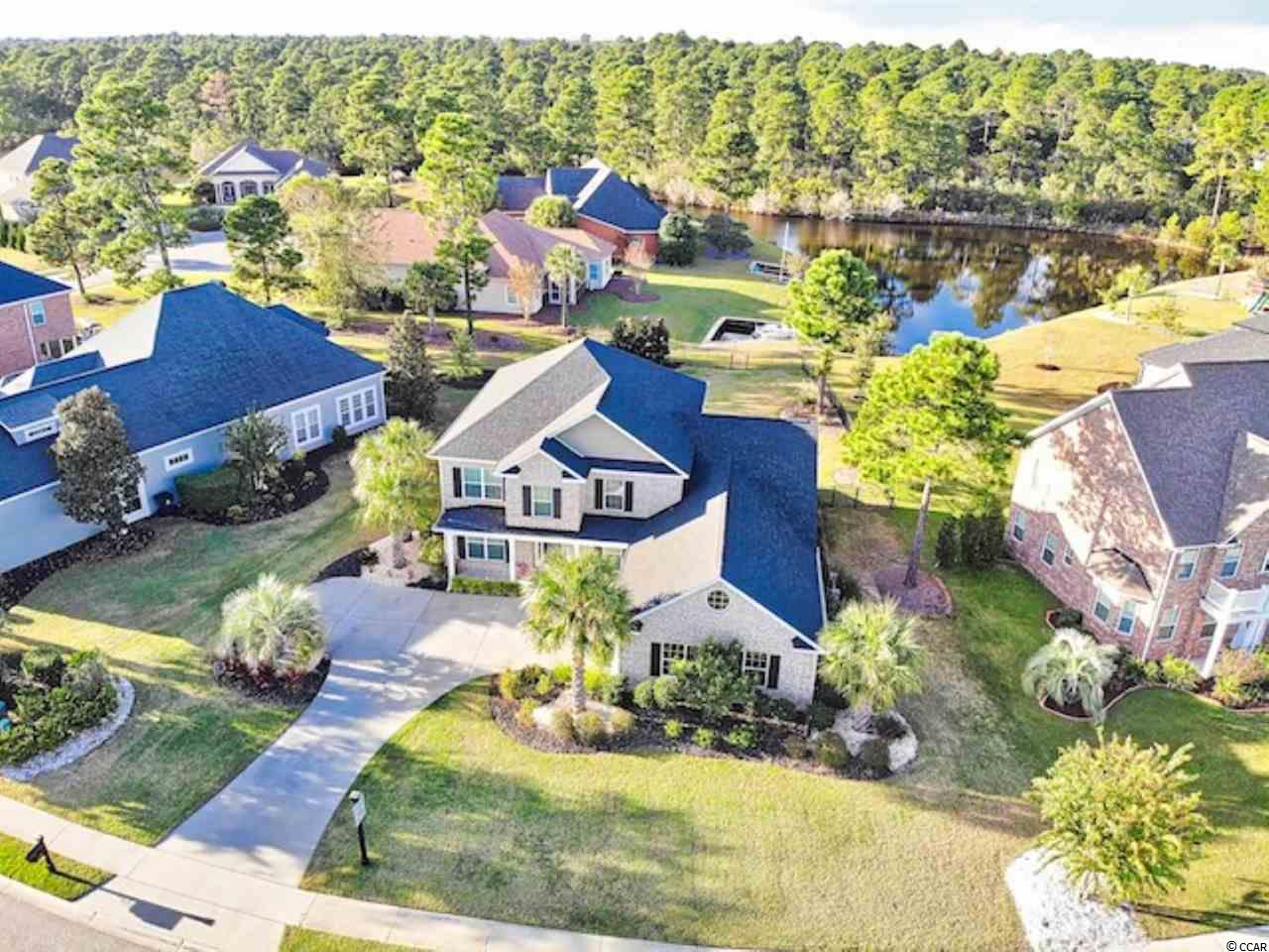 """Welcome home to this elegant, 5 bed 3 ½ bath, all brick home in the desirable Plantation Lakes community! The vast lot offers a 126' wide frontage and fully fenced back yard that backs up to water views. You will be thrilled with the modern coastal interior, tiled """"hard-wood"""" flooring throughout the first floor. Home has the option for a formal dining room or sitting area as well as a den/office area separated by French doors, giving you plenty of versatility with these rooms. The spacious first-floor master bedroom has a double tray ceiling with ceiling fan, walk-in closets and an en-suite bath with a large garden tub, double sinks, and a walk-in shower. Upstairs gives you a generous loft connecting 4 large bedrooms and 2 full baths. Enjoy the lovely South Carolina weather relaxing on the oversized screened-in privacy porch. This home is landscaped beautifully with tech-controlled irrigation and security systems- many more upgrades. Plantation Lakes residents enjoy the community pool, tennis courts, a clubhouse and a convenient dock for lake travelers. The location is just minutes from all the dining, entertainment and shopping that the Grand Strand has to offer!"""