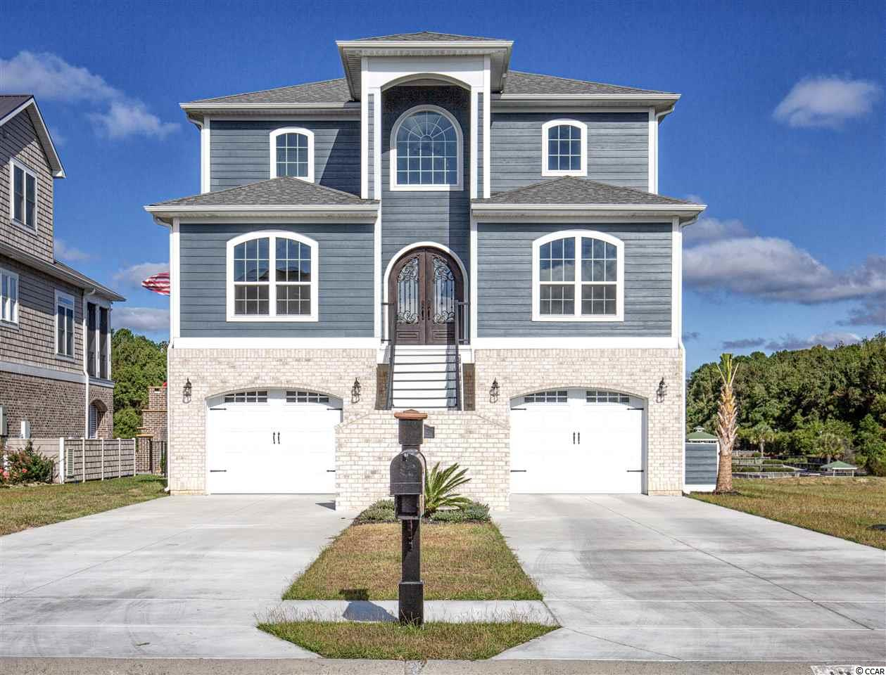 Immaculate like new 5 bedroom 3.5 bath home on the Intracoastal Waterway, just completed in May of 2019! This stunning home sits on the largest lot in the community and has all the bells and whistles; it is a SmartHouse and EcoHouse! Some of the amazing and practical features of this home include a security system, Hurricane windows/doors rated for 250 mph winds, 2 tankless hot water heaters, ceiling fans in every bedroom, granite countertops in all the bathrooms, waterproof engineered hardwood flooring throughout the entire house, and Timbertech Azek composite decking on the porches that has a limited lifetime warranty! The front steps take you up to the second floor, which is the main floor, where you are greeted by the exquisite wooden and wrought iron detailed front door imported from Italy! Once inside the cozy foyer you will notice the charming floor to ceiling wainscoting inviting you in. The open concept living and kitchen are flooded with natural light from the 3 sets of double glass doors that lead out to the porch overlooking the waterway. The living room features an elaborate diamond coffered ceiling, built-ins, and a 84in electric fireplace! The dining area is adjacent to the living room and has a tray ceiling. The gorgeous kitchen boasts white and grey marbled granite countertops, stainless steel appliances, beautiful pendant lights, a work island with seating, and a large walk-in pantry! On the main floor there are 2 bedrooms, a full bath, a powder room, and the laundry room. Upstairs on the third floor is the master suite as well as 2 more bedrooms and an additional full bath. One of the bedrooms on this floor is currently being used as an office and features lovely wainscoting trim. In the fabulous master bedroom you will find a coffered ceiling, a 60in electric fireplace, and 2 sets of french doors leading out to the 3rd floor porch also overlooking the waterway! The luxurious master ensuite has double sinks, a linen closet, a water closet, a 6ft free standing garden tub, and a lavish marble shower with 2 shower heads and a bench! The master suite also offers a dreamy and massive walk-in closet with built-in shelving & storage system! Down on the first floor is a partially finished very spacious room that could be a mother-in-law suite, a pool house, or a recreation room your choice! There is also an oversized 26ft long, 2 car garage with a golf cart garage! Outside brick archways lead you out to the concrete patio surrounding the 25x12 salt water pool with overflow hot tub! The pool is heated and cooled so you can enjoy it year round! This fenced in backyard will quickly become your favorite place to be with breathtaking views of the waterway, plenty of space to relax and grill plus this is even an outdoor TV! This lot also comes with a dock and boat lift permit included saving you money and time so you can build it to suite your taste and boat size! This magnificent house is located in Palmetto Harbor in North Myrtle Beach, close to popular spots like Barefoot Landing and Tanger Outlets and is less than 10 minutes from the beach!! Don't miss the opportunity to own this dream home, schedule your showing today!