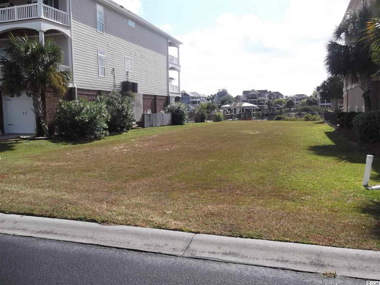 This is a vacant lot in one of the most prestigious gated communities in our area. Directly on the waterway with a shared dock that is already built. Two beautiful homes on each side if the lot. Owner will consider owner financing for a qualified buyer. Only a few minutes to the beach near shopping, entertainment ,many restaurants, many golf courses and all the beach and water activities at your finger tips. This is an exclusive community with very low HOA fees. You can have your boat right in your back yard on deep water and go out anytime you would like. Also has a floating dock for jet skis. You can go fishing right off your own dock. I does not get any better than this living directly on the waterway.