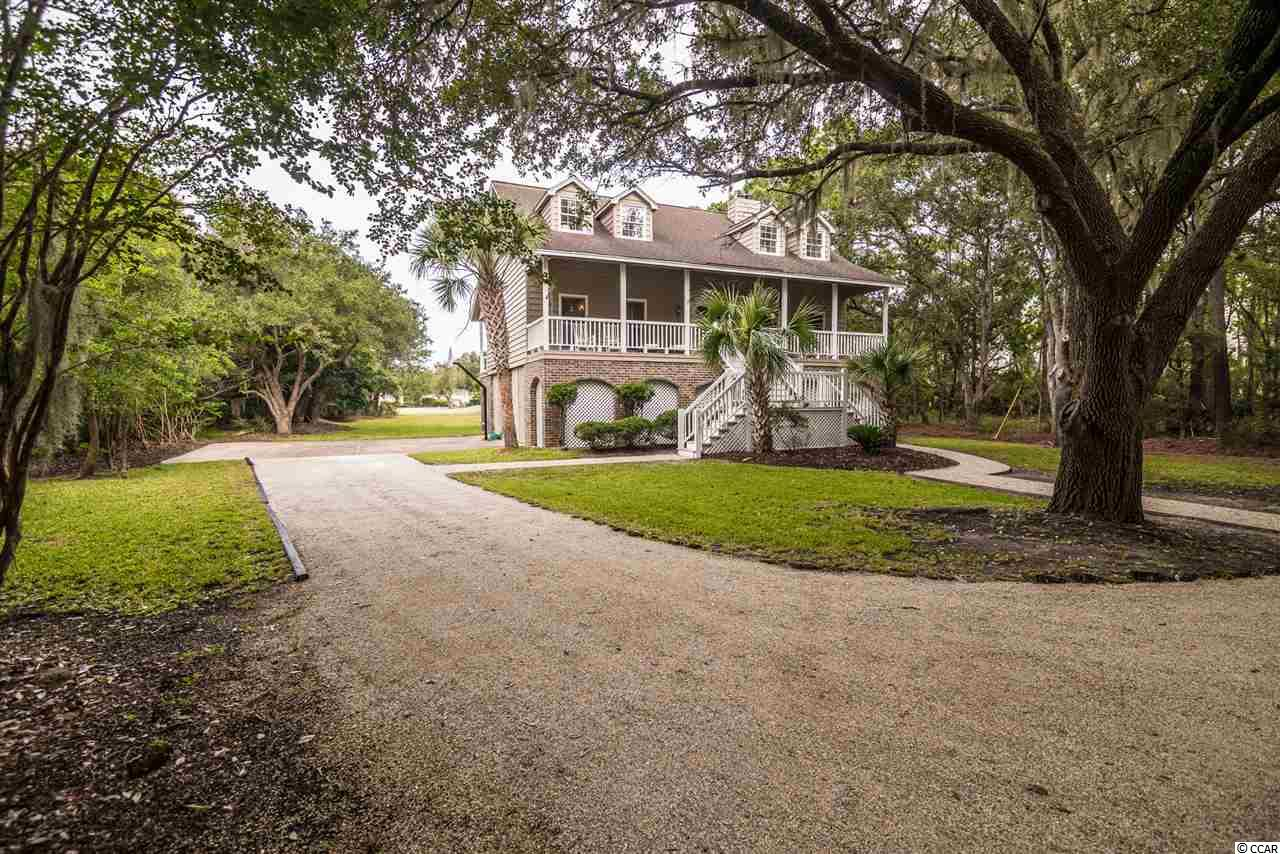 """This is a fantastic opportunity for you to own a spacious home in the beautiful DeBordieu Colony community.  This lakefront home offers 3 bedrooms and 3 baths and it's just moments from the ocean.  There is a huge back porch where you can look over the rear of the property and all of the moss-draped Oak trees. Sometimes from this area; late in the afternoon, you can enjoy the parade of turkey and deer as they make their way home.  There you will also find plenty of room for a pool and hot tub, if desired.  The front porch is the width of the home and provides a shady area to relax after a """"stressful"""" day of golf or tennis.  There is a community boat landing in DeBordieu Colony.  From here you have access to some of the best fishing, shrimping and crabbing in the area.  A kayak or paddleboard are perfect for exploring the creeks and canals of DeBordieu.  A unique feature of this residence is the abundance of wood throughout.  The kitchen is loaded with the modern appliances of today, but the natural wood gives you the feel of the older beach cottages.  There's a wood stove located near the wet bar.  Imagine a cool fall night; curling up on the couch with a hot beverage and enjoying the smell of burning oak and hickory. The amenities of DeBordieu Colony are unparalleled: including a World Class Golf Course, designed by Pete Dye; a remarkable Tennis Facility and an Ocean Front Pool and Recreation Area along with much more. The Golf Club house has a great bar and restaurant, and don't forget the Beach Club and outside Bar.  DeBordieu Colony; more than a community... It's a lifestyle.   Make plans to view this beautiful home today."""
