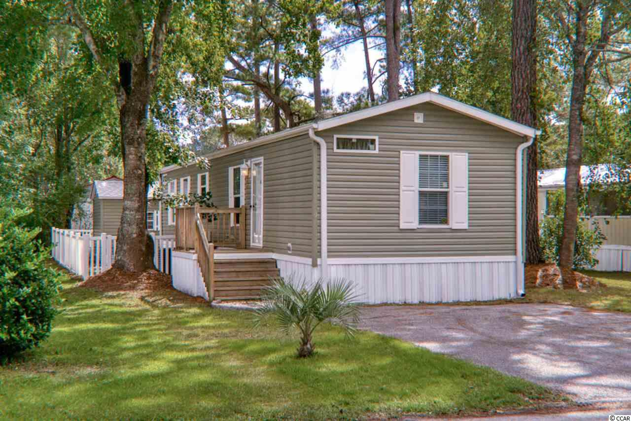 This 2016, 2 bedroom 2 bath home features a split bedroom plan, screened in porch, fenced in yard with a detached shed that matches the home. This shed is able to store a lifted Golf Cart, the ramp is already in place! As if this is not enough can you believe this leased property has irrigation! The home is located in Windjammer Village which is approximately 1.5 miles to the ocean a true golf cart ride away, and is priced to sell!  All measurements and Square Footage are approximate and not guaranteed. Buyer is responsible for verification.