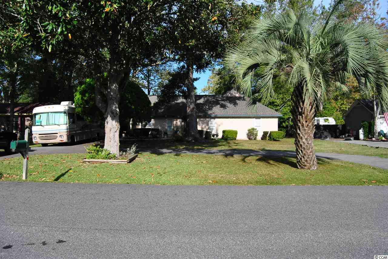 Come see this Beautiful, Well Kept 3 Bedroom, 2 Bath Ranch Style Home, just a Golf Cart Ride to the Beach! This Home has a Den, that can be used as a Formal Dining Room, as well as a  Huge 12 x 17 Carolina Room. This Home sits a on a Large Lot of .33 Acres with Mature Trees and plenty of room for parking, whether it is Cars, RV's. Boats, or Trailers. Also there is a Storage Room on the side of the Home, under the Carport, as well as a Utility Shed out back for your Lawn Mower and Tools. The Patio is 18 x 18 and plenty of room for sitting outside and enjoying the fresh air!!! You can also Entertain on the 11 x 22 Deck. Close to Shopping, the Beach, and many Restaurants! Don't let this one slip by! Make an Appointment to come and see this Home. You get the Beach, without the Beach Price!!!