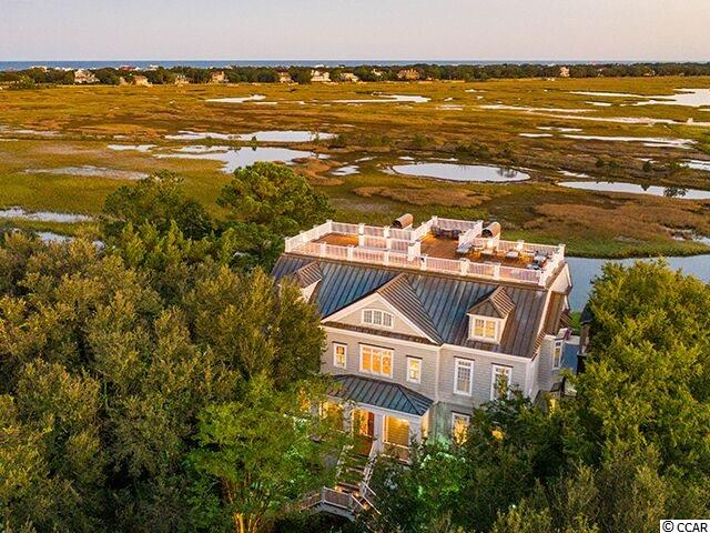 """DeBordieu Colony – A spectacular creek front home with a private dock and panoramic marsh views, 3278 Luvan Blvd. is a beautiful  7,000 Htd. Sq. Ft. masterpiece on the main channel leading to DeBidue Creek, North Inlet and the Atlantic Ocean.  As you step inside the towering foyer you're greeted immediately by the thoughtful design, top quality construction and that amazing view. The great room on the main living level is perfect for family gatherings of any size and is beautifully designed with a coffered ceiling, custom millwork, heart pine floors and cabinetry surrounding the gas fireplace. At the heart of the home is the gourmet kitchen featuring custom cabinets, granite and travertine countertops, top-of-the-line stainless steel appliances, 6 burner Viking gas cook top, double Thermador ovens and warming drawer, Subzero refrigerator, huge pantry, breakfast bar and breakfast room. Whether hosting an intimate gathering or a large crowd, you'll enjoy the butler's pantry/wet bar in the center of everything featuring a thermostatically controlled wine room. Also on the main living level are two guest suites, powder room, and laundry room. With all floors accessible by elevator, the master suite is located upstairs where the view is even better, and features a fireplace, separate vanities, walk-in closets, private water closet, large shower and jetted tub. Also on the third level are two more guest suites, a creek front den with fireplace and marsh view, and a media room. The 4th floor houses the gym, game room, wet bar, 2nd powder room, and an office with gorgeous pine paneling, fireplace and creekfront deck. The 4th floor provides easy """"push button """"access to the roof top deck, from which you can see the ocean, creeks, and marshes of North Inlet one of the most pristine estuaries on the East Coast, teeming with fish. Outdoor entertaining opportunities abound with the full """"summer kitchen,"""" the pergola with wood burning fireplace, and the gorgeous infinity pool. The"""