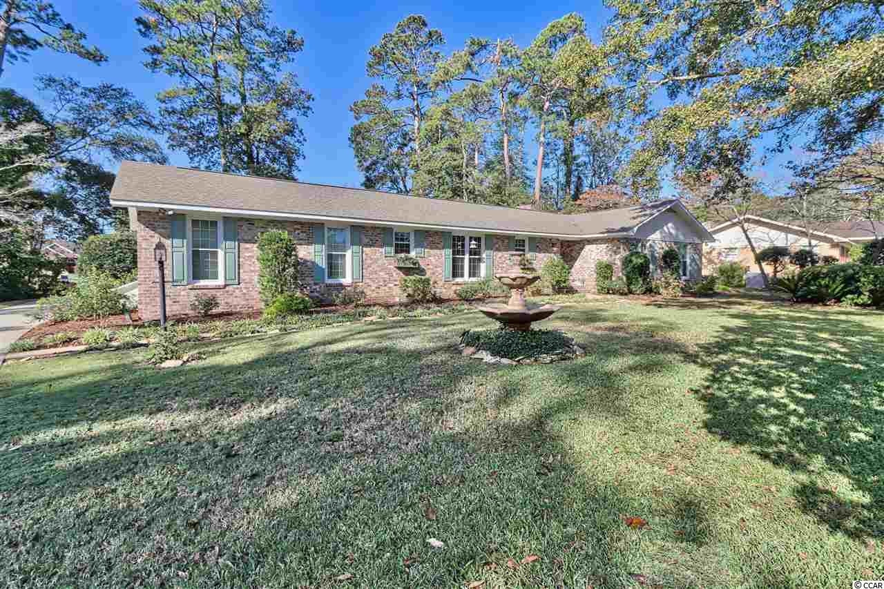 Located in desirable and unique Cedar Creek Village, this well-kept 3 bedroom, 2 1/2 bath, all brick home is situated on .40 acres. Cedar Creek Village is an Intracoastal Waterway community consisting of custom homes, each expressing its own character, having side or rear loading garages and spacious yards. The HOA allows homeowners to bring boats with accepted guidelines.  The home is surrounded by mature trees and landscaping with front and backyard fountains. Azaleas and dogwood trees create a small parklike setting on the front side of the home.  The 8x12 storage building has a recently added extended roof which allows for outdoor dining or grilling, while the backyard patio boasts outdoor string lighting for nighttime enjoyment.  The home features a rear loading garage having approximately 740 square feet and its own 1/2 bath. Inside features include custom trimmed windows, double french doors to the screened back porch, a skylight in the living room, brick fireplace with gas logs, and a sitting or office nook off the breakfast dining area.  Located within minutes to the beach, marinas, restaurants and the quaint Little River fishing village.