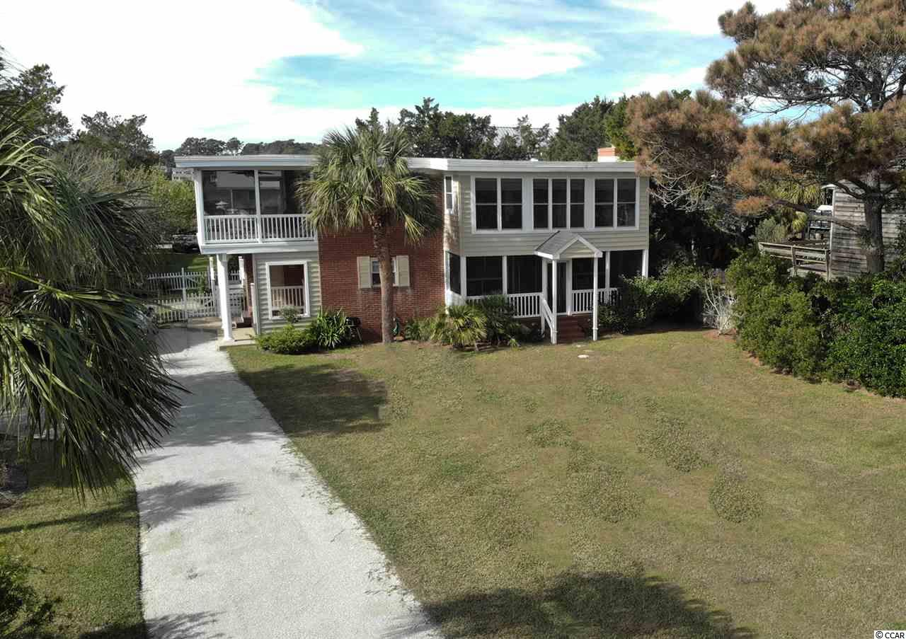 The finest off ocean home on Pawleys. Second row on the growing north end of Atlantic Avenue. This is the only brick home on Pawleys! Built to last and it has. A town recognized duplex that is a great rental income producer and allows owners to also come and go as they please. Convenient beach access is close bye and just around the corner is the boat ramp for Pawleys Creek. Location, Location, Location.  An extra large lot allows for multiple parking, boat storage or future expansion.  The upstairs and downs stairs have separate exterior entries but the house can be used as a single now with the addition of an interior staircase with lockable access.  The owners have taken great care in furnishing and keeping this home in mint condition. Each level of the home has a modern kitchen, living and dining areas, 2 bedrooms and bath, screened porch. Downstairs has a real fireplace. Upstairs has a large sunroom on front. Upstairs porch has views of Pawleys Creek.  A turnkey home fully furnished and including items for rental occupancy. Ready now. But hurry!