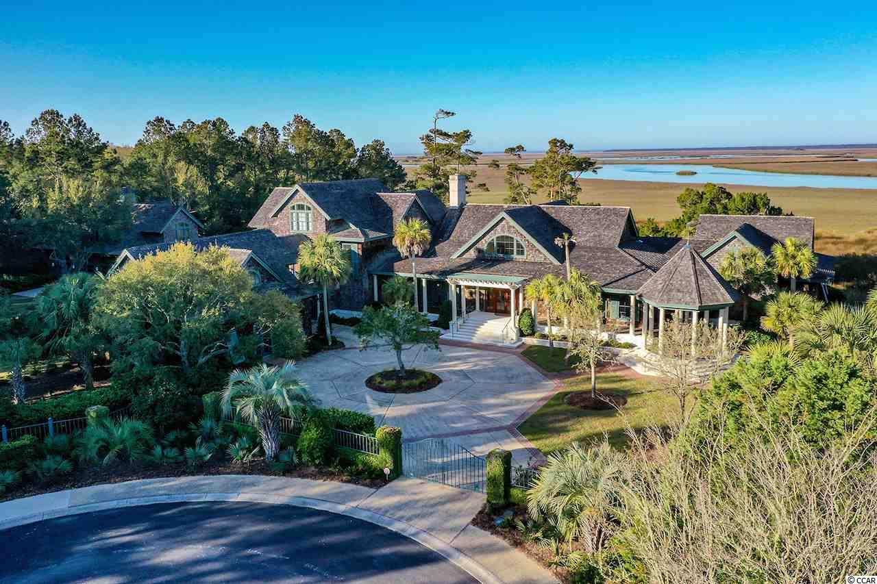 """Overlooking the North Inlet National Estuarine Reserve, one of the most pristine and protected estuaries in the world and the third largest by area on the East Coast, this beautiful waterfront estate offers a truly unequaled private setting. Located within DeBordieu Colony, a gated oceanfront community with low density and private club facilities, the beach is only a short walk away while the magnificent undisturbed views of thousands of acres of creeks and marsh plus your own private deep-water dock are just outside. Adjacent to the home is the oceanfront portion of Hobcaw Barony, a 17,000-acre undeveloped estate owned and protected by the Belle W Baruch Foundation. The historic seaport of Georgetown is nearby while Charleston can be reached in little over an hour.  Numerous exquisite custom details abound throughout the luxurious West Indies style home. Fine woodwork is perhaps the most prevalent and impressive of the homes many fine features, but the overall finishes, quality of construction and attention to detail are more typical of a yacht than a home. The open interior makes the most of the beautiful Lowcountry views while encouraging access to the expansive outdoor living areas and saltwater pool. Inside, the spacious bedrooms and suites are arranged in wings designed to both promote and protect privacy keeping separation from the living and entertaining areas.  Unique features of this home reflect its South Carolina coastal location. Room for the storage or collection of multiple vehicles, golf carts and boats is incorporated in both the garage and separate """"boat house."""" A dedicated tackle room allows for the storage and maintenance of fishing gear, paddle boards or other hobby items. The multiple porches and decks allow for enjoying the enjoyment of the outdoors with the company of others or for moments of private time and reflection. The dock features both fixed and floating dockage as well as a new boat lift. Being sold mostly furnished with personal exc"""