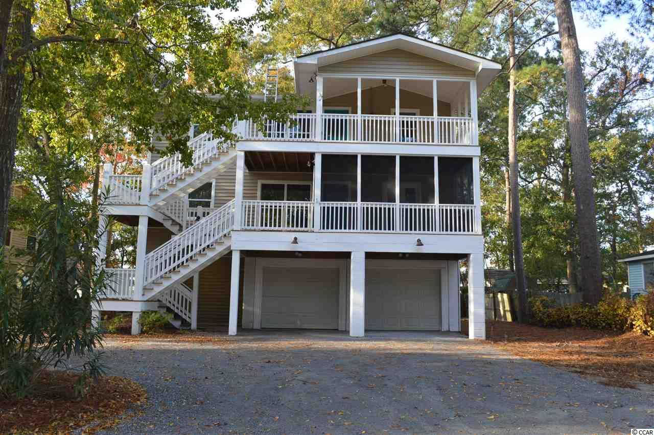 This beautiful duplex has just had an EXTREME MAKEOVER and is in perfect move-in condition! If you are a beach lover, you will be thrilled to know that it is just a short stroll or golf cart ride to the blue Atlantic! No HOA- another plus! This is NOT your usual duplex as it's a delightful mix of beachy and new combined which you will absolutely love!  If you are looking for a great investment property or a full-time home, look no more, you have just found it! Live in one unit and lease out the other, the choice is yours. Both units have three bedrooms and two full bathrooms. Top floor unit has vaulted and beamed ceiling in the living/dining room area and features a cozy wood burning fireplace which is so nice for those chilly evenings!  Walls and flooring in this area are Heart pine therefore it  gives this unit that warm and inviting feeling. Walls in other rooms have been freshly painted in colors that are very pleasing to the eye.  Kitchen is spacious and has been completely updated with refinished cabinetry, new stainless-steel appliances, new light fixtures, sink, faucets and gorgeous granite counter tops. The chef will love preparing their meals in this great kitchen! New carpeting in bedrooms, ceiling fans and light fixtures throughout. Master bathroom has been updated with new commode, luxury plank flooring,  beautiful walk-in tiled shower and sliding glass door. Guest bath has new tub with stylish tile surrounding it. New commode and luxury plank  flooring. Most windows have just been replaced. A large covered front porch is the perfect place to retreat to as there you may sit and relax and take in those great ocean breezes! Lower unit has also been completed updated and renovated and now looks like new! A open floor plan greets you as you enter through the screened-in porch into this lower  unit.  Beautiful luxury vinyl plank flooring throughout that certainly gives this unit that upscale look which you will love!  There is an extra room off the living ro
