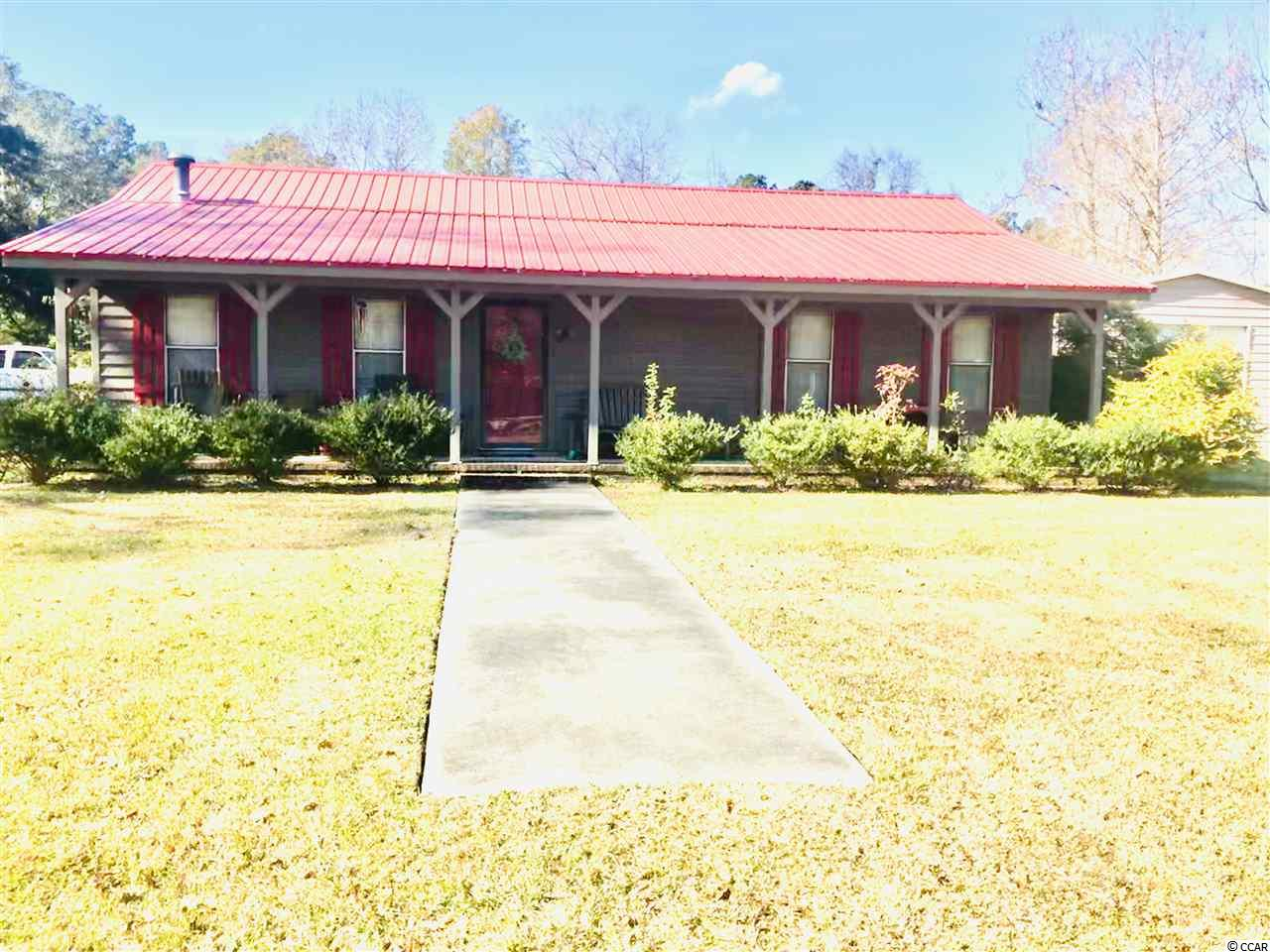 Who doesn't want a house with a red roof and a front porch as wide as the house?! The Lakewood neighborhood in the Kensington area of Georgetown is close to historic downtown without being in the city limits. This cute country style home sits on a corner 1/2 acre lot on a quiet street. An attached side load garage with a storage room is not the only place to store the car, boat, camper or motorcycles. The 24' x 30' shop, with it's on driveway, has plenty of room for all the toys! Rock on the front porch all day and by night sit by the fire pit on the patio in the privacy fenced in backyard where your furry friend can run around. Vaulted ceilings in the family room and the dining room make them feel even bigger than they already are. Both rooms also have built in shelving and storage. In the family room they line both sides of the wood stove and its brick accent wall. This 20' x 14' dining room can easily accommodate a 10-12 chair table.   If you love the red roof and shutters you'll love the kitchen cabinets too. They are also painted red!  Stainless appliances, breakfast bar and room for a breakfast table make for a roomy kitchen. The master bedroom is a great size with an on suite bathroom and walk in closet. The second bedroom is just as roomy with an extra door to the larger than normal hall bathroom.  Conveniently located just inside from the garage is a 1/2 bath and the laundry area. And did I mention that 24 x 30 shop?!!!! Home Warranty for 1 year from the Seller. NO HOA!  Square footage is approximate and not guaranteed. Buyer is responsible for verification.