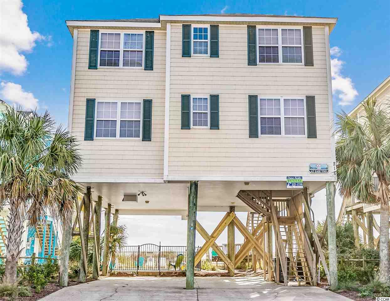 218 North Waccamaw Drive, known as At Ease Too, is located oceanfront in Garden City Beach. The home is six bedrooms, six bathrooms, measures 2544 heated square feet and comes with a private heated pool. The interior is well maintained, and the owner has made improvements that will make this raised beach house feel like a home. On the main level, there is a large oceanfront kitchen, dining area, and living room that leads to a screened-in porch offering access to your private beach access. The well-appointed kitchen is highlighted by granite countertops and white cabinets. There are also two bedrooms, two full bathrooms. Upstairs you'll find an additional living room, four more bedrooms, and four full bathrooms. The master suite and living room have access to a second oceanfront screened-in porch. The exterior is wrapped in vinyl ceding shake siding, parking for at least six cars, and a fenced-in yard with pavers surrounding a new gunite pool. The property is situated on a recently re-nourished beach with multiple dunes and healthy sea oats. You're just steps north of the Garden City Pier, the small downtown restaurant district, and minutes to all Myrtle Beach has to offer. The home is currently on a vacation rental program and producing income that can offset the owner's carrying costs. The rental history is available upon request. Why continue to rent when you can own your very own beach retreat.