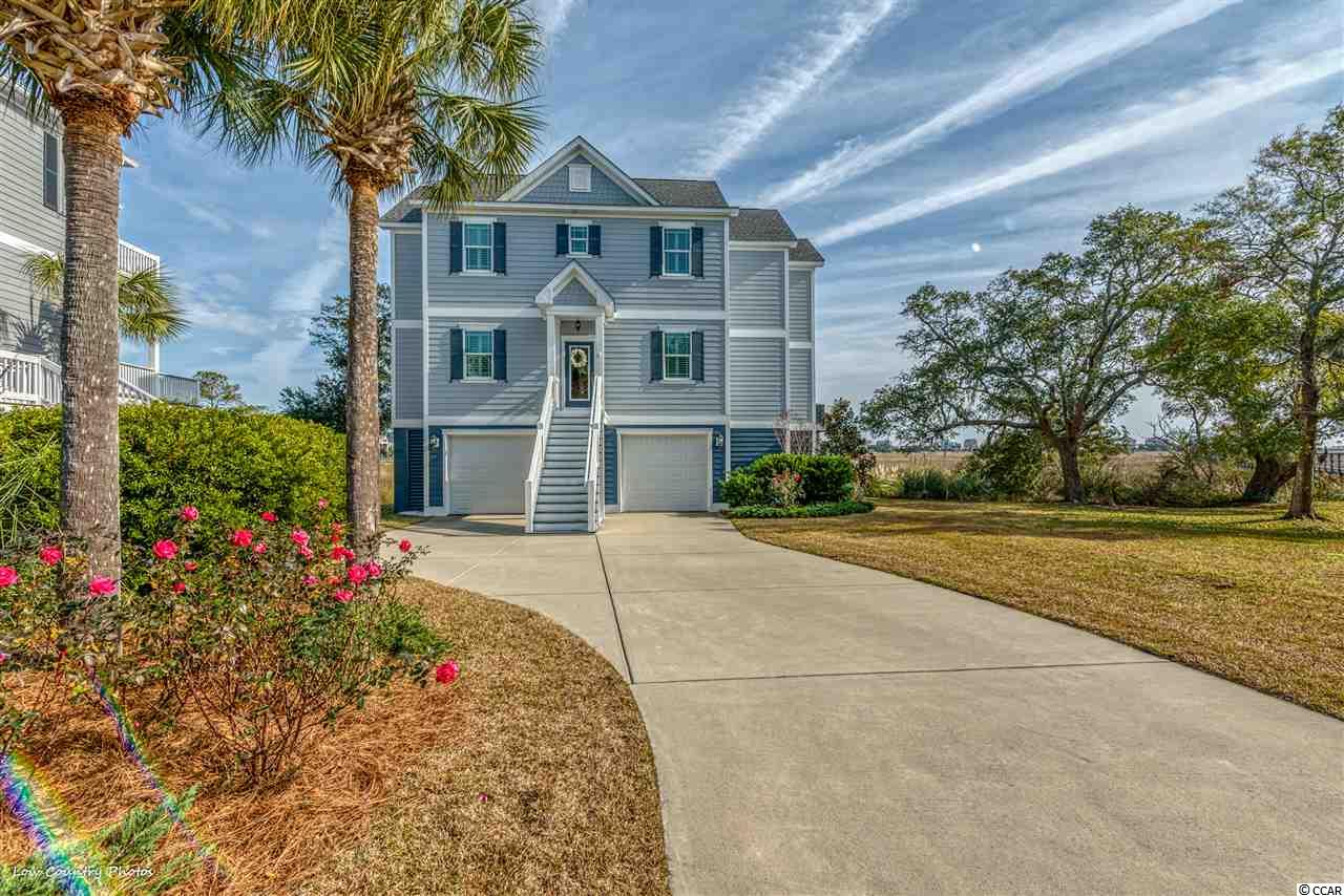 """168 Windy Lane is a unique offering of modern efficient construction and  design that leverages the best of beach living with magnificent views of the inlet, marsh and ocean of Litchfield and Pawleys Island, SC. This wonderful home was constructed in 2016 and incorporates an inverted floor plan with outstanding features far above the norm including: elevator, impact hurricane windows and doors, tank-less water heater, Hardy- board siding,  LED lighting, fireplace and much more. A quick ride up the elevator drops you off on the top floor living space with an open floor plan and breath taking view from every vantage spot.  The large living room features a fireplace and opens to a wonderful covered porch overlooking the inlet. The living area flows to an open dining and kitchen featuring granite counter top, stainless appliances, and wonderful large island with window wall views of the marsh. The top floor is completed by an office/den with marvelous glass doors and a large storage room. Down a level, the second """"sleeping"""" floor features the master suite with private porch and large walk-in closet, two bedrooms and bath plus a spacious and efficient laundry room. Special care was invested in the bath rooms featuring porcelain tile, walk in showers with frame-less glass enclosures, and granite counter tops. The ground level contains secured parking and lots of storage and an intimate covered patio. Thoughtful design, superior construction, meticulous maintenance make living easy, the view makes living a dream come true!"""