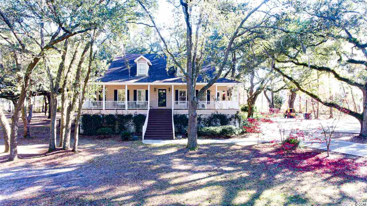 Located within Wedgefield Plantation community, this 4 bedroom, 3.5 bathroom home has a stunning 3.57 acre lot backing up to a marsh off the Black River. This beautiful raised beach house style home includes a formal dining room, living room with high vaulted ceilings and fireplace, a Carolina room and bonus mother-in-law suite on the ground level. The first floor master suite has rear patio access, a large walk in closet, master bathroom with a walk in shower, inviting jetted tub and his and her vanities. The second floor hosts 3 additional bedrooms and 2 baths providing ample room for family and guests. The mother-in-law suite has a bedroom and bathroom with a large flex space that could be utilized as a living space, playroom, office or gym area. Also located on the ground level is a workshop or storage area approximately 350 sq ft and ample additional storage area under house. On the property you will find numerous beautiful old oak trees giving this property a uniquely peaceful setting. Wedgefield Plantation offers memberships which include many great amenities that include the Manor House for dining, golf club, pools, community boat ramp and much more! Conveniently located just outside the city limits of historical Georgetown, South Carolina where you can enjoy waterfront dining, shopping, touring the harbor walk and the many historical site. Square footage is approximate and not guaranteed. buyer is responsible for verification.