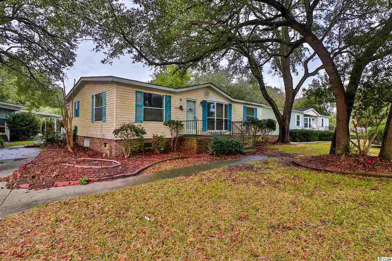 GREAT OPPORTUNITY in the sought after Live Oak 55+ Community! LOW HOA and you own the land! This 3 bedroom, 2 bath doublewide needs some work, but was being lived in until November and could be a way to get some sweat equity while living in the home. This has a beautiful Carolina room on the back that overlooks the back yard and patio, part of the common area, and the neighborhood salt water pool that you get to enjoy without maintaining. Normally, it would be very difficult to get into this community at this price! Close to the beach, the marshwalk, the amazing restaurants, and more! Opportunities like this disappear fast!