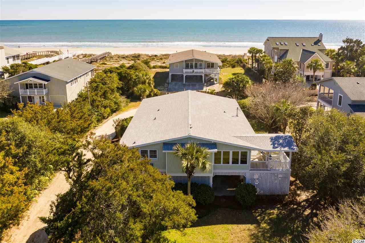 """This classic 5 BR home, with its inviting front porch and breathtaking ocean views, is situated on a quiet road directly across from desirable North Litchfield Beach and just steps to beach access. This home is on the ocean side of Parker Dr. making it much closer to the beach than 2nd row homes on the west side of Parker Dr. (more like """"1.5 row""""). So close to the beach! Sit and relax while enjoying your favorite beverage on the spacious front porch that adds a wonderful extension of the indoor living areas to the outdoors. This home boasts a beautiful coastal decor and is fully furnished.  You will love the stunning details of this perfectly planned Lowcountry style home including vaulted ceiling with exposed beams, hardwood floors in living area, built-in shelving and fireplace with North Litchfield Beach seashell surround and mantel from an old SC barn. This home had an addition and many updates in 2009 including larger bathroom with marble tub surround and vanity top, main floor laundry room and extended living area. Two of the five bedrooms are located on the ground floor with central heat and air.  Most recent updates include new roof (2017), HVAC, refrigerator and garbage disposal (2019). New glass in front door and exterior painting were completed in 2018. This home is on a spacious homesite and should have plenty of room for a pool. Underneath this raised beach house, you will find plenty of parking space and storage for beach toys such as boats, surfboards, kayaks, golf cart, etc.   This lovely property at North Litchfield Beach, also known as a bird watcher's paradise, is conveniently located to Brookgreen Gardens and other beautiful beaches of the Atlantic Ocean such as Pawleys Island and Huntington State Park, restaurants, shopping, art galleries and medical facilities. North Litchfield Beach is known to be one of the best kept secrets on the east coast.  For those seeking an active lifestyle, there are miles and miles of bike trails and many world clas"""