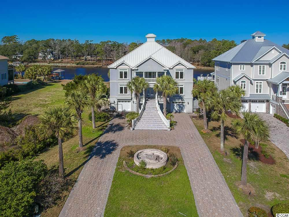 This is an absolutely EXQUISITE house on the Intracoastal Waterway. A curved circular paver driveway brings you to this 4 Bedroom, 3 Bathroom home in the upscale Harbour Watch community in North Myrtle Beach. The highest quality features are built into this spectacular home with generous sized rooms. The interior is beautifully appointed.  Beautiful glass front entry doors welcome you into a very open floor plan with tiled floors, a Family/Great Room with beautiful wooden built-in cabinets, a Fireplace and a Formal Dining Room. The Kitchen is a cook's delight with gorgeous wooden cabinets with a pecan finish, tiled backsplash, Stainless Steel appliances, Granite Counters, a center Island plus Breakfast Bar, an extra Oven, pendant & recessed lighting and more! The Master Suite is an oasis all of its own! The Master Bath has dual sinks, a large walk-in, tiled Shower, plus, a whirlpool tub for relaxing. There are 4 Decks. One has a Hot Tub for your enjoyment. There is a private dock and floating platform for your boat! There is a private Elevator to all levels. No HOA fees! This house offers the BEST in Southern living! There is too much to list!! This is a must see!!