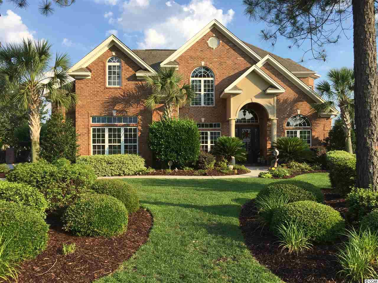 Enjoy lake front living at its best in this beautiful, executive home located in Myrtle Beach's premier neighborhood of Plantation Lakes. This well designed, open concept home sits on a one acre lake front lot. With 5 bedrooms, 3 1/2 baths, two story great room, formal living & dining room, office & media room offers many options for your family to be together or to enjoy some privacy.  As  you pull up to the house you will first notice the elegant curb appeal of the traditional all brick home with an oversized 3 car garage, large paver driveway and walkway to the front door.  Upon entering the home into the 2 story foyer, you will immediately take note of the attention to detail in the extensive crown molding,  8 inch base boards, intricate rod-iron staircase and the glowing hard wood floors. To your left is an office/library well positioned for privacy, formal living and dining room on your right which leads through to the Chef's Kitchen, with maple, hand-crafted custom cabinetry, granite counter top and GE Profile stainless appliances, large sit up counter/bar and eat in breakfast nook, all open to the large 2-story family room which is enhanced by beautiful built in entertainment center and fire place.  Also on the main level is a large laundry room also with custom cabinetry and located adjacent to the master wing which is maintained at perfect temperature with its own heating and cooling system. The master bedroom features a sitting area and french doors leading to an elegant master bath with tiled shower, whirl pool tub and separate his and her vanities. As you head up the stairs to the 2nd floor you will find an open lofted hall way over looking the 2 story family room. On the right are large guest bedrooms separated by a full Jack and Jill bath featuring a private water closet. On the left is  two more large bedrooms, also separated by a full Jack & Jill bath. One of these rooms is currently being used as an entertainment room with a pool table. Through this room is a media room wired with 7.1 surround sound. Sit down and relax. No need to go out to the movie theatre when you will become completely immersed in the sight and sound of your movie of choice in your own home theatre. Through the house to the screened-in back patio, with ceiling fan, you will be awed by the sight of the Walt Disney World Resort inspired backyard retreat. The flow of water from the hot tub to the pool, as well as the waterfall and fountains, make this area an incredible oasis. A cool, calm breeze winds through various seating areas, one of which includes a fire pit. All of this is enhanced by the gorgeous, mature tropical foliage and landscaping. This tropical paradise is fully enclosed with wrought iron look fencing complemented with impressive brick pillars. In addition, there is a fenced in side yard where you can play football or croquet on the grass kept lush by a built-in sprinkler system. Further on to the lake is your private boat dock with boat slip. There are many amenities that show the planning, care and love that went into the building of this masterpiece. Economically, the water and sewage for the home has been separated from the water system for the pool, enabling savings of hundreds of dollars. The fireplace in the living room has the ability to heat the whole house, allowing you to not have to use the HVAC system, again a savings to you. The alarm system with security cameras with night vision can be controlled and monitored from your iPhone. Whether it is morning, afternoon or nighttime, your view is vividly clear. A whole-house entertainment system is accessible from keypads throughout the home. You can choose satellite radio in one room, any radio or TV station in another room. Don't delay in scheduling an appointment to see this one of a kind home, it won't last long!