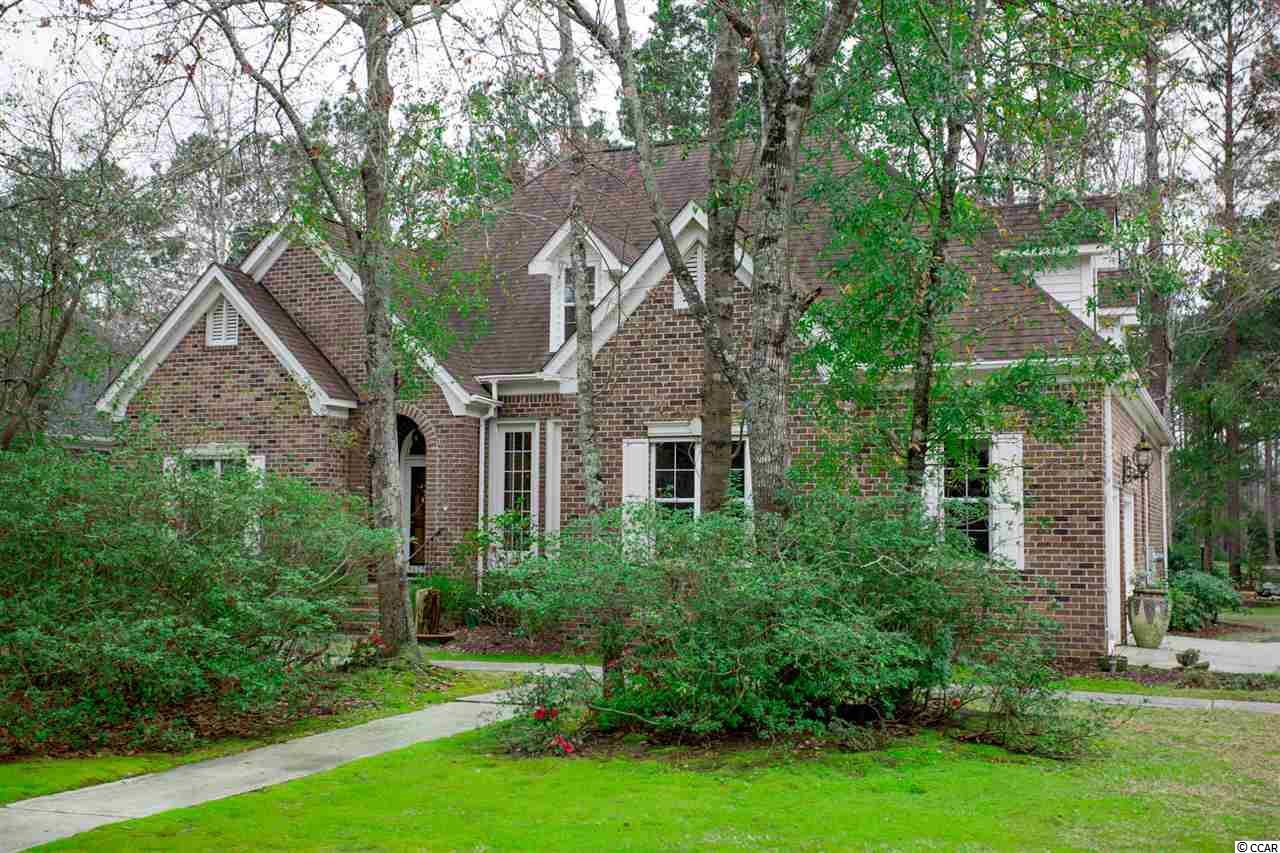 It's a Knockout! Unique, 5-bedroom (4 bedroom + bonus room) home, situated on a beautiful ½ acre lot in the estate section of the popular Indigo Creek community in Murrells Inlet.  Private, serene and Oh What A View! Absolutely beautiful setting w/ lush landscaping, over 100 azaleas, a reflective garden & goldfish pond.  Overlooking a lake & #5 Fairway at Indigo Creek Golf Course, this stately brick 1.5 story home has it all w/ upgrades galore.  The creativity of the talented artist who lives here shines through w/beautiful custom decorative wall & ceiling painting & finishes throughout. Attention to detail & pride of ownership are immediately apparent in this impeccably maintained custom home. Nestled among the trees, this home has great curb appeal & boasts quality throughout. As you drive up the long driveway, the tone is set.  Walk up a few stairs to the covered arched entry into the foyer w/attractive oak hardwood flooring which leads into the living rm w/ soaring ceilings, a floor to ceiling brick, gas fireplace, tile floor, ceiling fan, recessed lighting, & decorative shelving.  Completely remodeled kitchen will be a chef's delight with granite counter tops, tile floors, custom cabinets, recessed lighting, stainless steel appliances including a double oven & cooktop range, pantry, breakfast bar & breakfast nook.  Formal dining room with wood trim, tile & large floor to ceiling windows overlooking the front yard.  Laundry room w/ tile floor, cabinets and utility sink.  Spacious office with built-in bookcases, vaulted ceiling, fan, wallpaper, carpet, pocket door and windows overlooking the front yard.  Master bedroom with luxury vinyl plank (LVP) flooring, tray ceiling, fan, walk-in closet and large floor to ceiling windows overlooking backyard.  Beautiful remodeled master bath suite with updated custom cabinets, vanity with granite countertop, separate porcelain tiled walk-in shower with glass door, porcelain tiled tub, stain glass window, LVP flooring, tray c