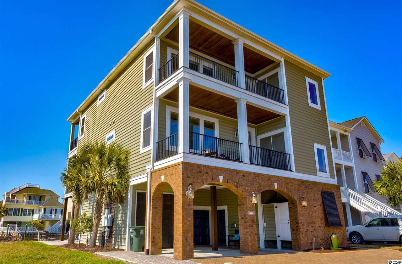 Gorgeous raised beach home in Cherry Grove that sits directly on the channel. This home has been beautifully designed to accommodate a family by having large rooms, private bathrooms, and large storage closets.This home features beautiful inlet views through large windows, has a practical/spacious open floor plan, outdoor bluetooth speakers, automatic shades on the second floor, indoor/outdoor living at its finest, as well as a shared dock. Walking distance to Cherry Grove's Nature Preserve. Enjoy nights utilizing the fire pit overlooking the water, or cozy up by the propane powered fireplace inside or out. The backyard provides the ultimate outdoor living area with a functional space perfect for entertaining. This is the dream home you have been looking for!