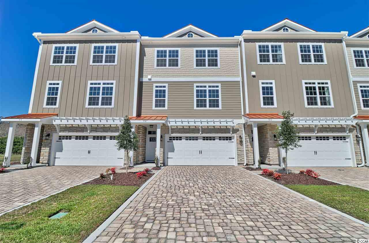 Majestic Oaks is a community which offers gracious and gated luxury townhome living in historic Murrells Inlet across from the marshfront. The public boat landing, the MarshWalk and all of the famous and fabulous restaurants are within walking distance. The beaches of Huntington Beach State Park and Garden City are only minutes away. These three story villas boast 3 or 4 bedrooms, two-car garages, rear porches, fenced in back yards, and offers natural gas. In Phase III many upgrades such as elevators, luxury vinyl plank flooring on all levels, wood shelving in all closets, shaker cabinets and more are now standard! This townhome features an open kitchen with a center island, a tiled tub surround in the first floor bathroom, a wet bar on the first floor as well as a tankless water heater.  Enjoy over 2700 heated square feet of living space with a community pool, all within a gated neighborhood. Call today to schedule an appointment to personally experience the newest lifestyle in the Inlet! 94 Oyster Bay Drive is move-in ready and is currently the furnished model for the community.  (Furnishings/window treatments do not convey)