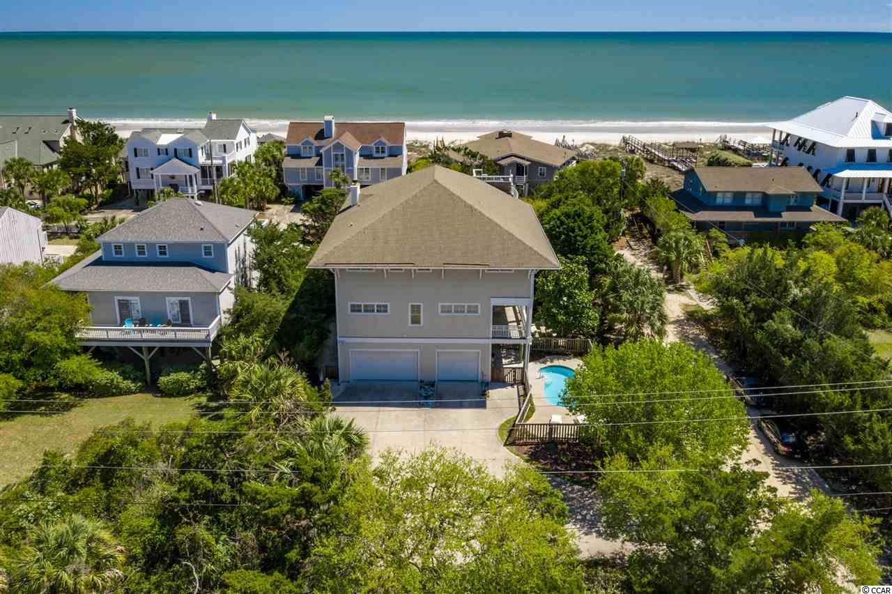 "Located in the ever-popular North Litchfield Beach, this beach home awaits its next owner.  Offering 6 bedrooms, 6 full baths, this raised beach home boasts ocean views from its many decks & sits less than 50 steps from the beach access.  After a fun day at the beach, come back to the house and relax in the private pool or enjoy a fire in the outdoor fireplace. Enjoy a book or cocktails from the widows walk while enjoying the panoramic views and ocean breezes.  This home is in pristine condition.  The spacious interior offers an expansive great room with vaulting ceilings, gas fireplace & more ocean views.  Just off the great room sits the gourmet kitchen that features stainless steel & granite counters, center island, breakfast bar, gas cooktop, oven w/ warming drawer, 2 dishwaters, wine cooler and stainless steel appliances.  The master suite is one to be desire.  This large suite features a walk-in closet and its own private French doors to the wrap-around porch and highlighted by the spa-like master bathroom.  Other interior bonuses include a 2nd den, elevator, washer/dryer sets on each living level, water purifying system & central vacuum.  In addition to the private pool & outdoor fireplace, the exterior is just as great for entertaining as the interior.  The expansive wrap-around porches house a large outdoor kitchen, pool table and several rocking chairs.  The driveway sets the stage with a ""half court"" adjustable basketball goal and the enclosed garage as plenty of room for 3 cars plus any outdoor toys you may have not to mention a large ice machine to keep up with the cooler demands in the hot summer months.  The carefree lifestyle at 21 Shorebird awaits."