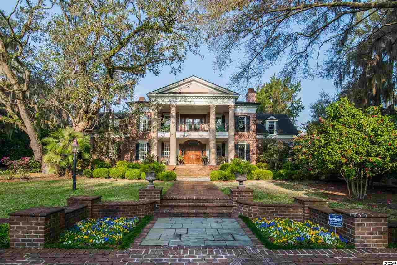 A notable 5 acre residence located between Charleston and Myrtle Beach SC, one of just 4 exclusive Lower Waverly estates surrounded by 80 acres of protected land, is nestled ceremoniously on the banks of the Waccamaw River, elegantly hidden behind a stately wrought iron gate with a winding 300 year old oak lined drive, exuding privacy.  A mesmerizing showcase of exquisite design and craftsmanship, the interiors feature walnut, cherry, mahogany, hickory, and poplar paneling, beautifully blended with custom millwork, stained lead glass, and brass and crystal chandeliers. Fabulous imported antique English tiles and Italian stairway railings add further luxury touches. Meanwhile, a grand home theater, designed as a nod to the 1920s, combines a historical aesthetic with the latest technology. Elsewhere, a superb kitchen exudes sophistication with custom cherry cabinetry, while two sumptuous master suites delight— both opening to gorgeous outdoor covered spaces. The main floor master suite delivers a splendidly opulent en suite bath and sitting room. Double terraces take sublime advantage of the breathtaking natural landscape, overlooking a mile of unspoiled Intracoastal Waterway and Waccamaw River. This opulent Pawleys Island estate, inspired by an 1841 Natchez, Mississippi plantation, with attention to detail at every turn and sweeping, incomparable views will delight the discerning art & real estate connoisseur.