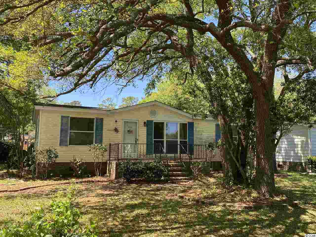 Perfect opportunity for homeowner or investor to purchase in the lovely Live Oak 55+ community. Low HOA fees and you own - not lease - the land! This manufactured home features a spacious living room with vaulted ceilings, a galley kitchen with dinette area, large master bedroom with attached master bathroom suite and walk in closet, two additional bedrooms, a hall bath, and a huge Carolina room off the back of the house. The back yard faces the common area and the community pool and clubhouse. Close to marshwalk, beach, and restaurants and shopping. Property will be sold via online auction - see agent notes.