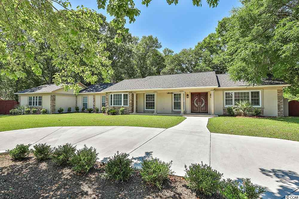 """Welcome home to this completely remodeled custom 4-bedroom home on a .51-acre lot just a few blocks from the beach in the desirable Arcadian Shores section of Myrtle Beach! No expense was spared on this one of a kind home.  All new landscaping and a new circle drive add to this home's curb appeal!   A beautiful double door entry leads through a stacked stone archway to a cozy formal living room with a beautiful stacked stone fireplace and tray ceiling with crown molding.  The upgraded kitchen features 42-inch cabinets, granite counter tops, gas range, stainless steel appliances and glass backsplash!  This """"no carpet"""" home features hardwood and tile flooring through the home.  The master bedroom of the home features a large walk in closet as well as a double tray ceiling.  The master bath features custom tile walls and shower with glass doors as well as a double vessel sinks!  A large family room sits just off the kitchen area and features several storage closets as well as a double door entry to the bright and airy Carolina room that can also be used as a fourth bedroom! A motorized gate leads from the driveway to the spacious and private fenced back yard which is a lovely green space with plenty of shade from the afternoon sun and features a huge patio area off the Carolina room.  Other features of the home include a dedicated laundry room, 2 car garages, upgraded plumbing, new fixtures throughout, new stucco/stacked stone exterior, sprinkler system and detached storage building.  Arcadian Shores is an optional HOA community just a short distance from the popular shore drive area and features free beach parking as well as a beautiful lake front pier overlooking the community pond!"""